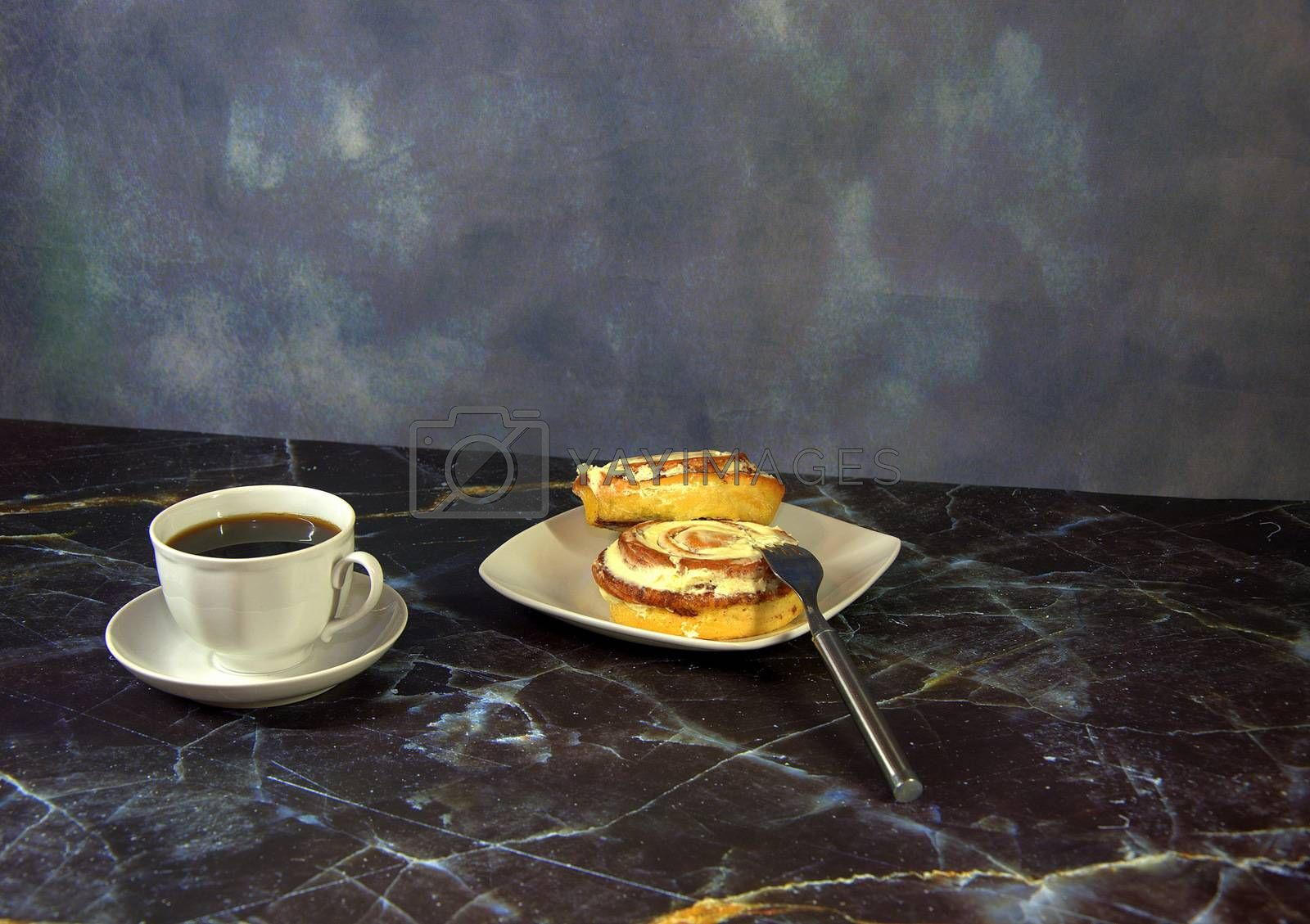 A cup of black coffee on a saucer and bwe cinnamon rolls on a plate, next to a fork. Close-up.