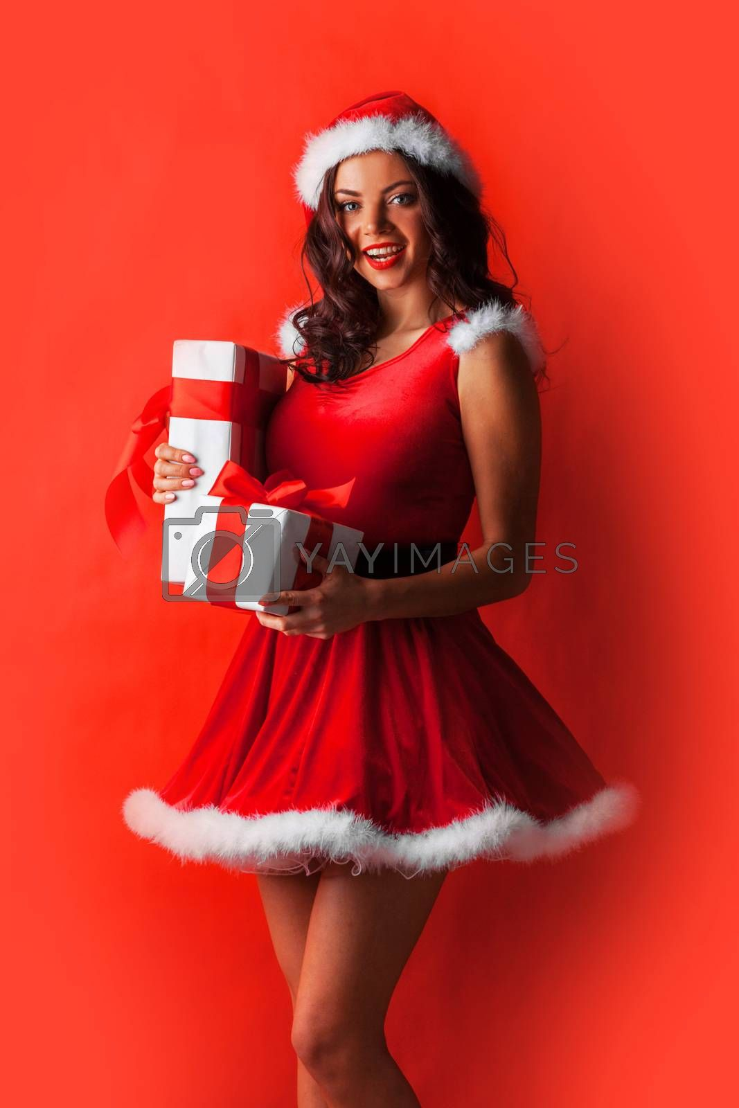 Smiling cute girl in red christmas outfit holding gift boxes