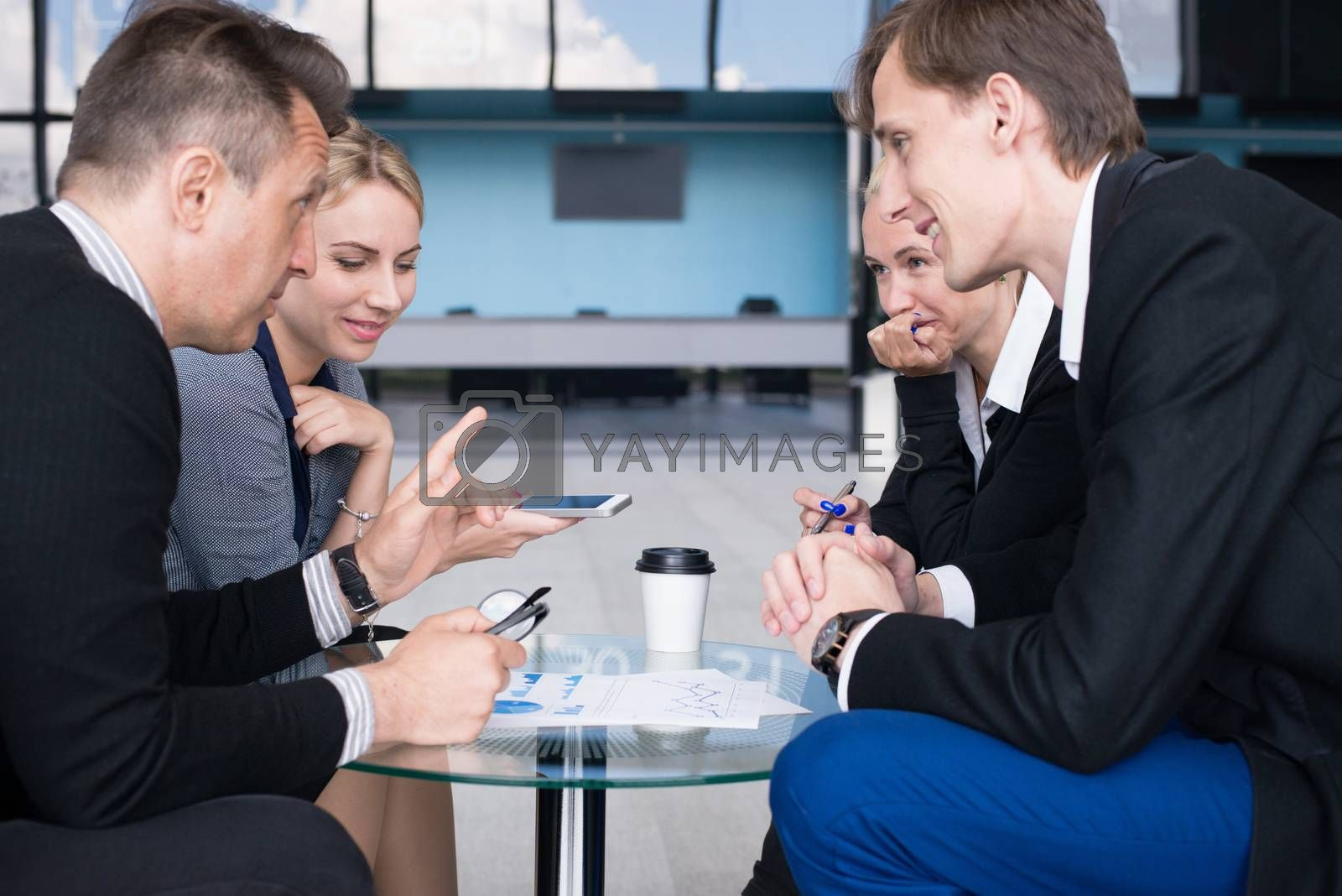 Portrait of happy business people talking at break in cafe sitting together at the table