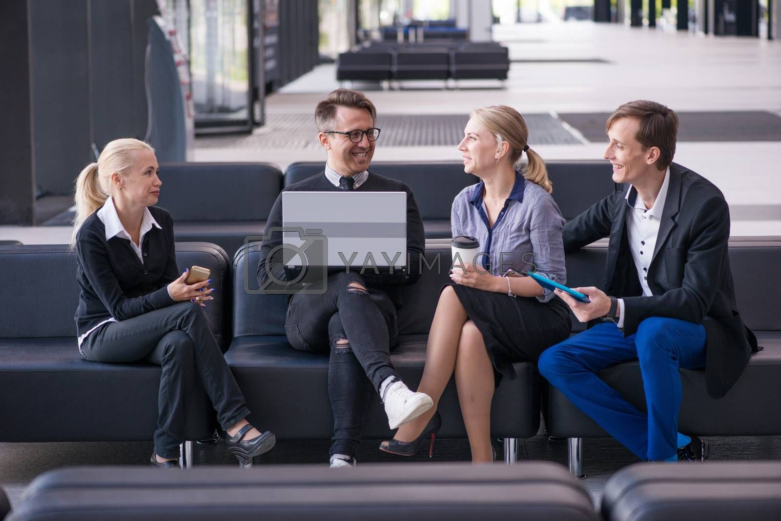 Portrait of happy business people talking at break in business center lobby sitting together at sofa