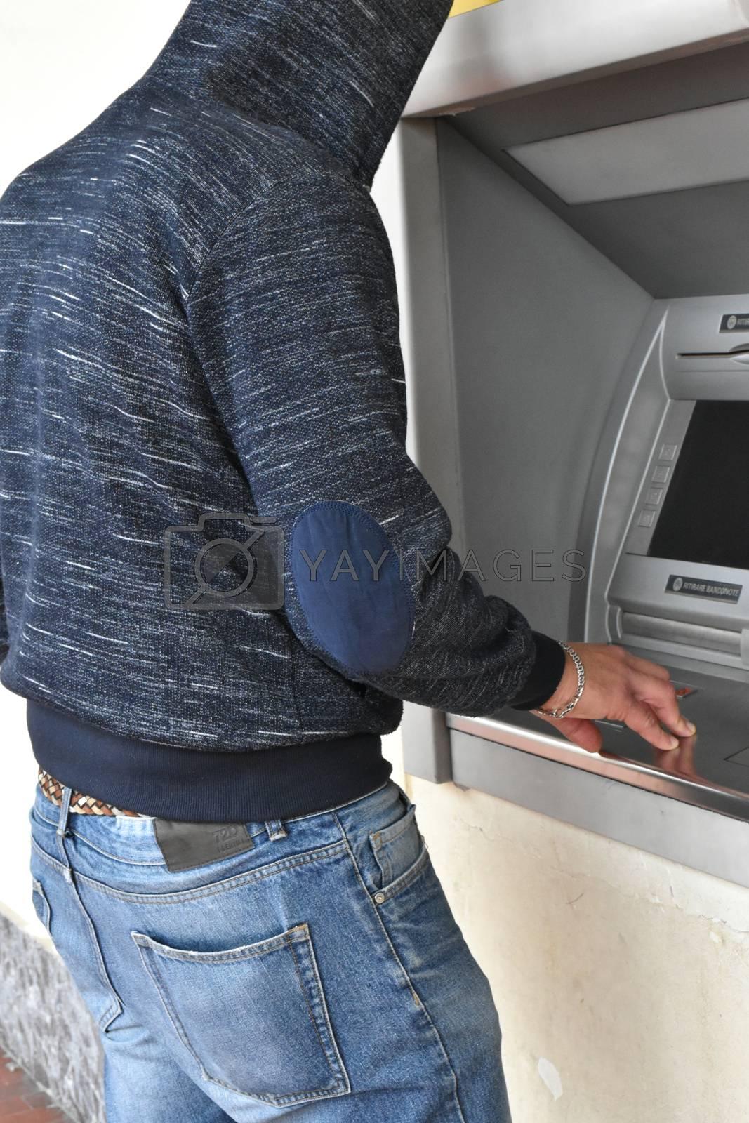 Man while rubbing a cash machine atm
