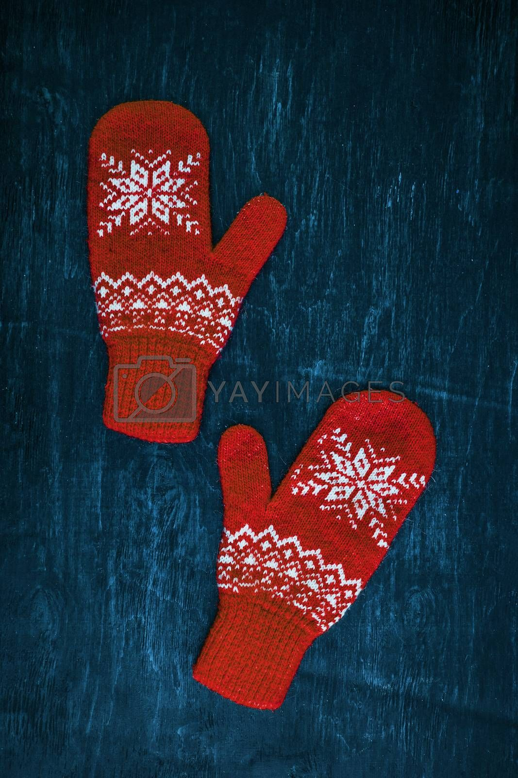 Royalty free image of a pair of red-pink-lilac-magenta purple knitted mittens on a dark blue-green-brown wooden by Tanacha