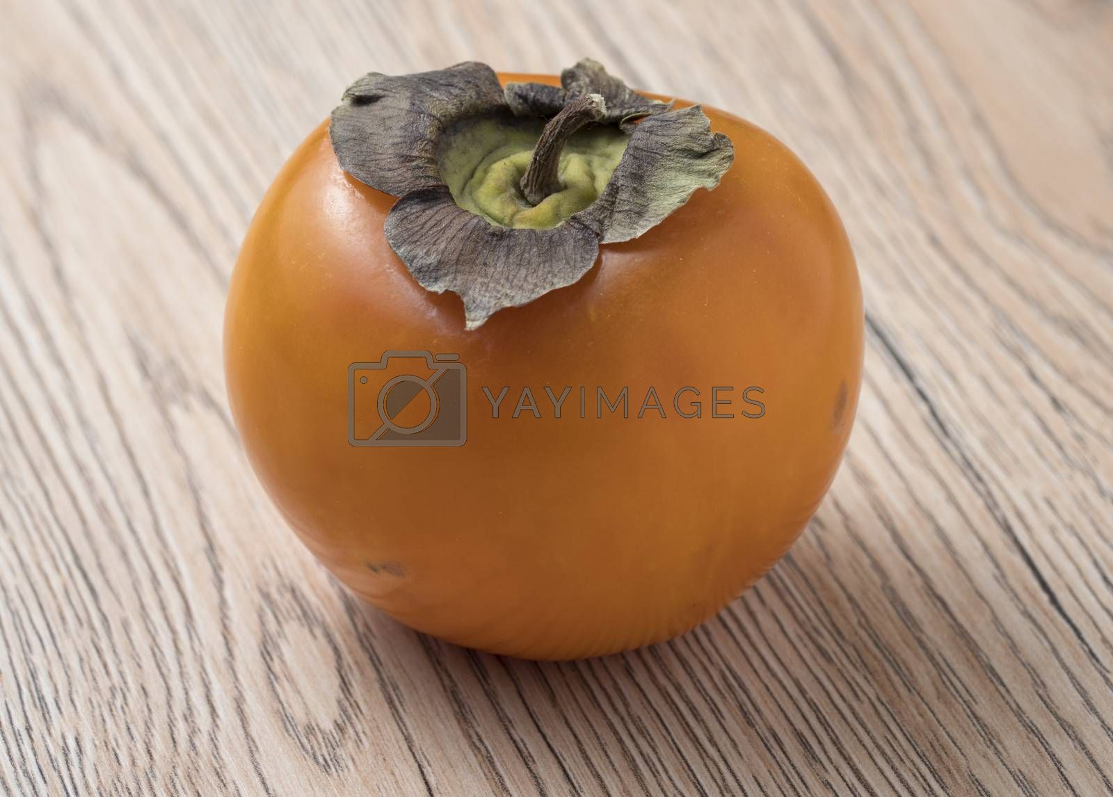 Royalty free image of Whole ripe persimmon fruit on wooden background. by phortcach