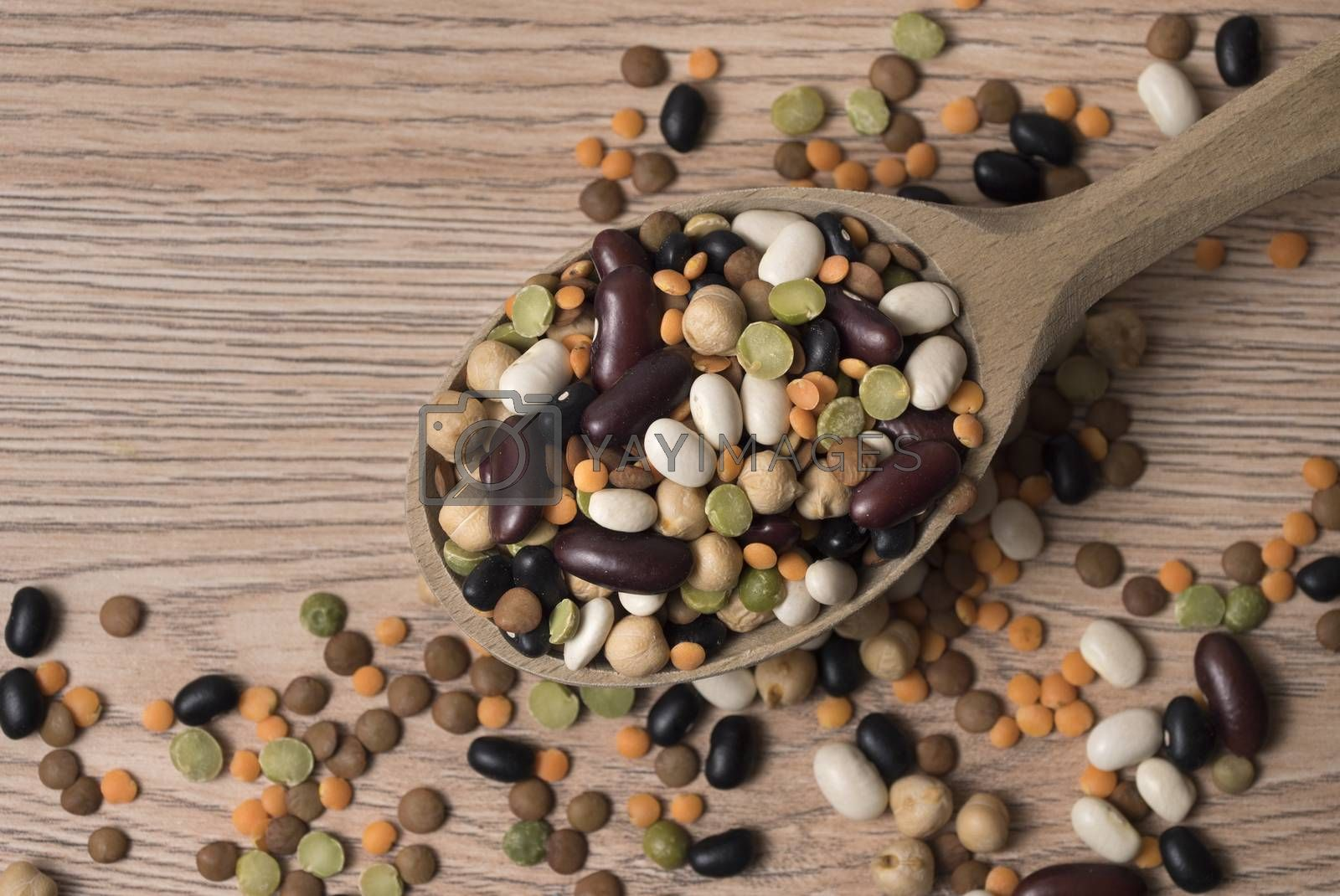 Royalty free image of Legumes of various kinds in a wooden spoon on the table. by phortcach