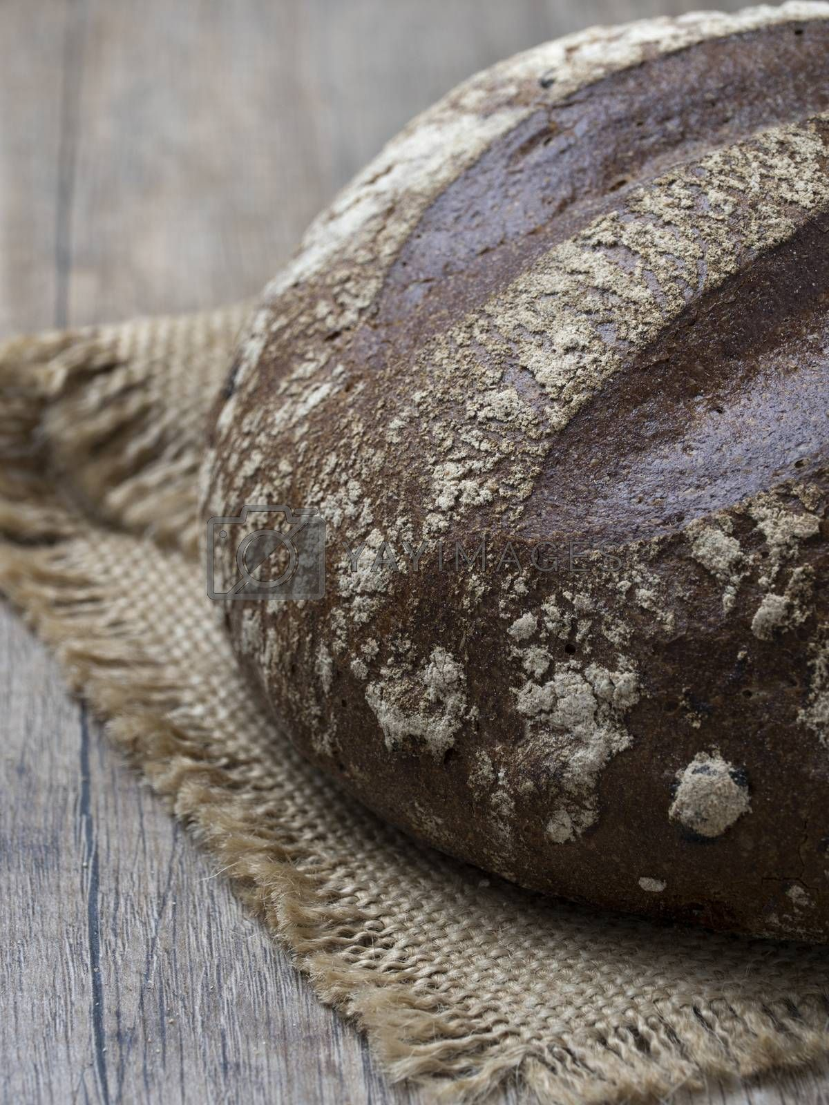 Royalty free image of Round loaf of freshly backed sourdough bread on wooden backgroun by phortcach