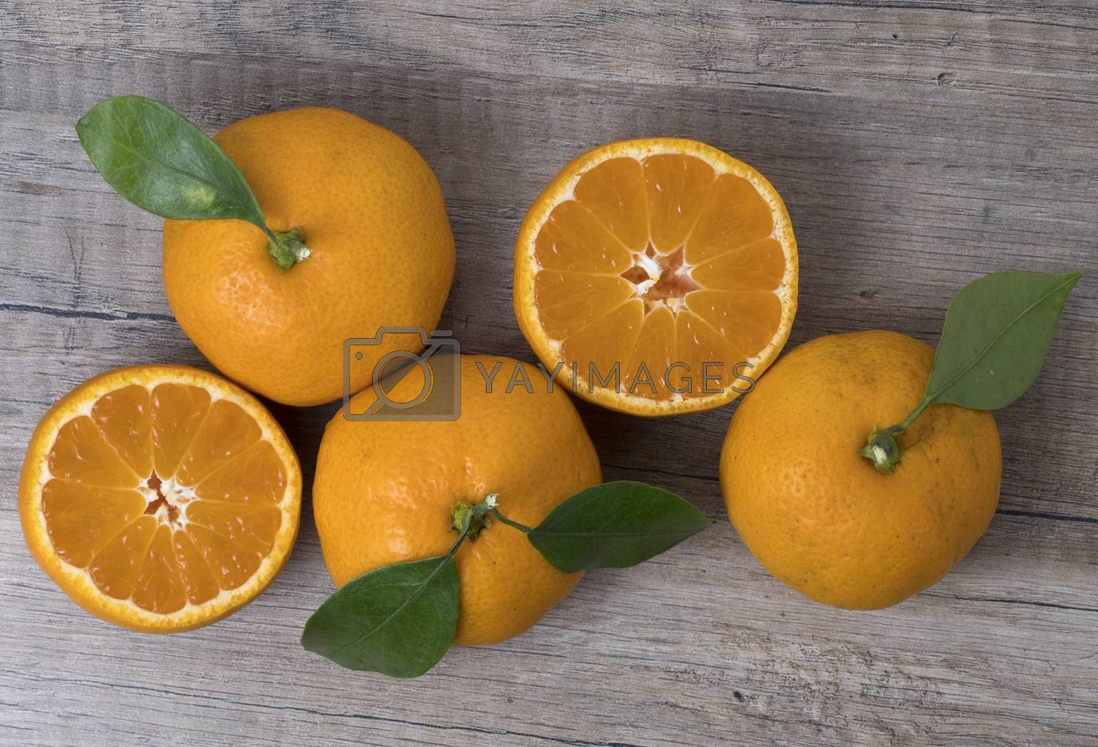 Royalty free image of Fresh ripe tangerines with leaves on a wooden background. by phortcach