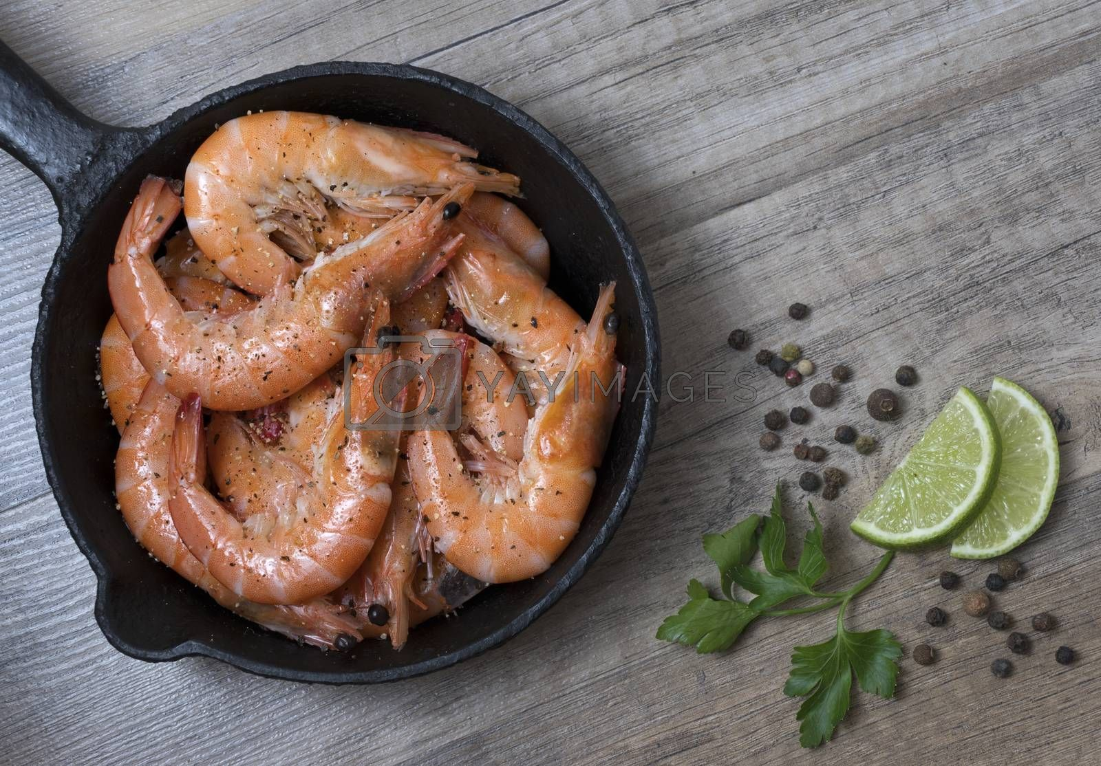 Royalty free image of Grilled prawn shrimps in a frying pan with spices, on wooden bac by phortcach