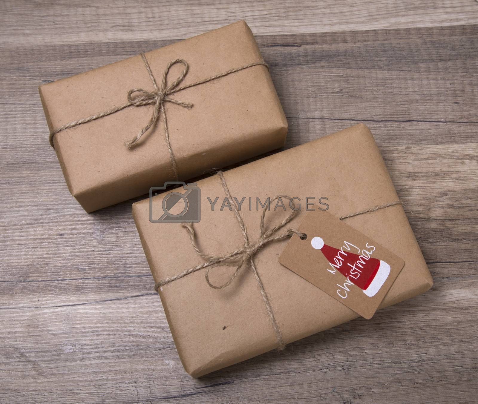 Royalty free image of Christmas gift boxes wrapped in kraft paper, with blank gift tag by phortcach