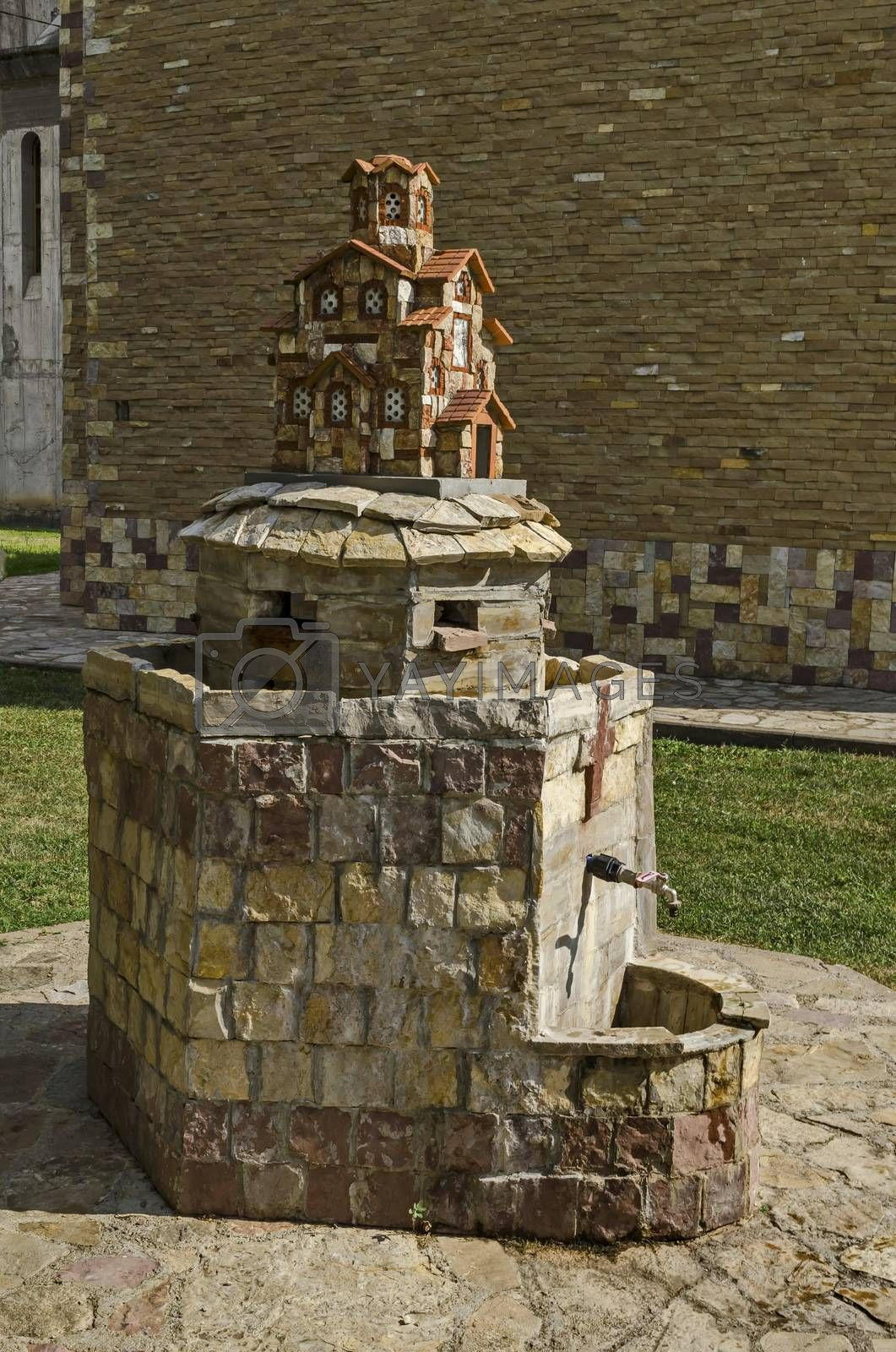 Royalty free image of Fountain  with miniature of  orthodox church at the back in public garden, town Delchevo by vili45