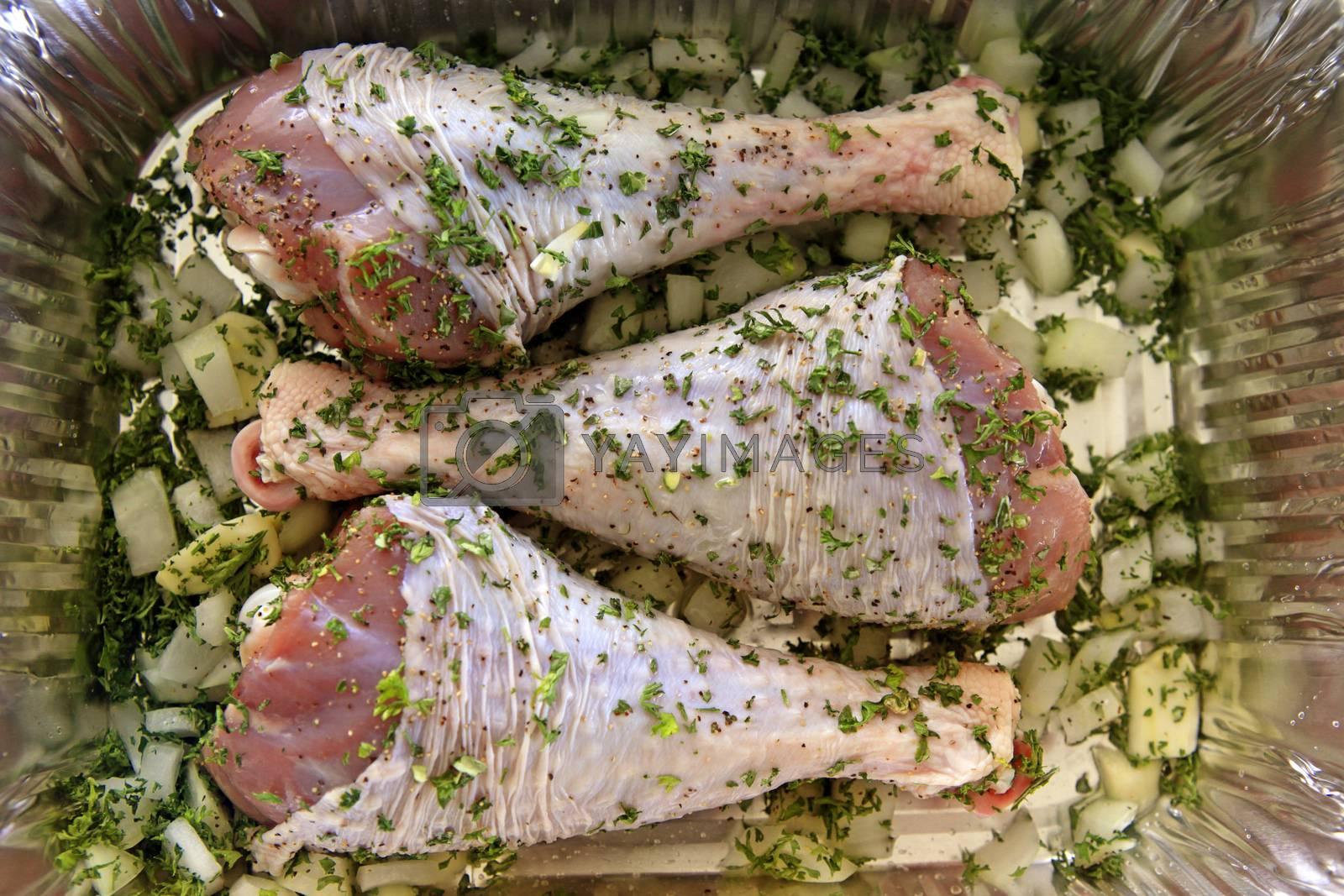 Turkey leg on steel board with herbs
