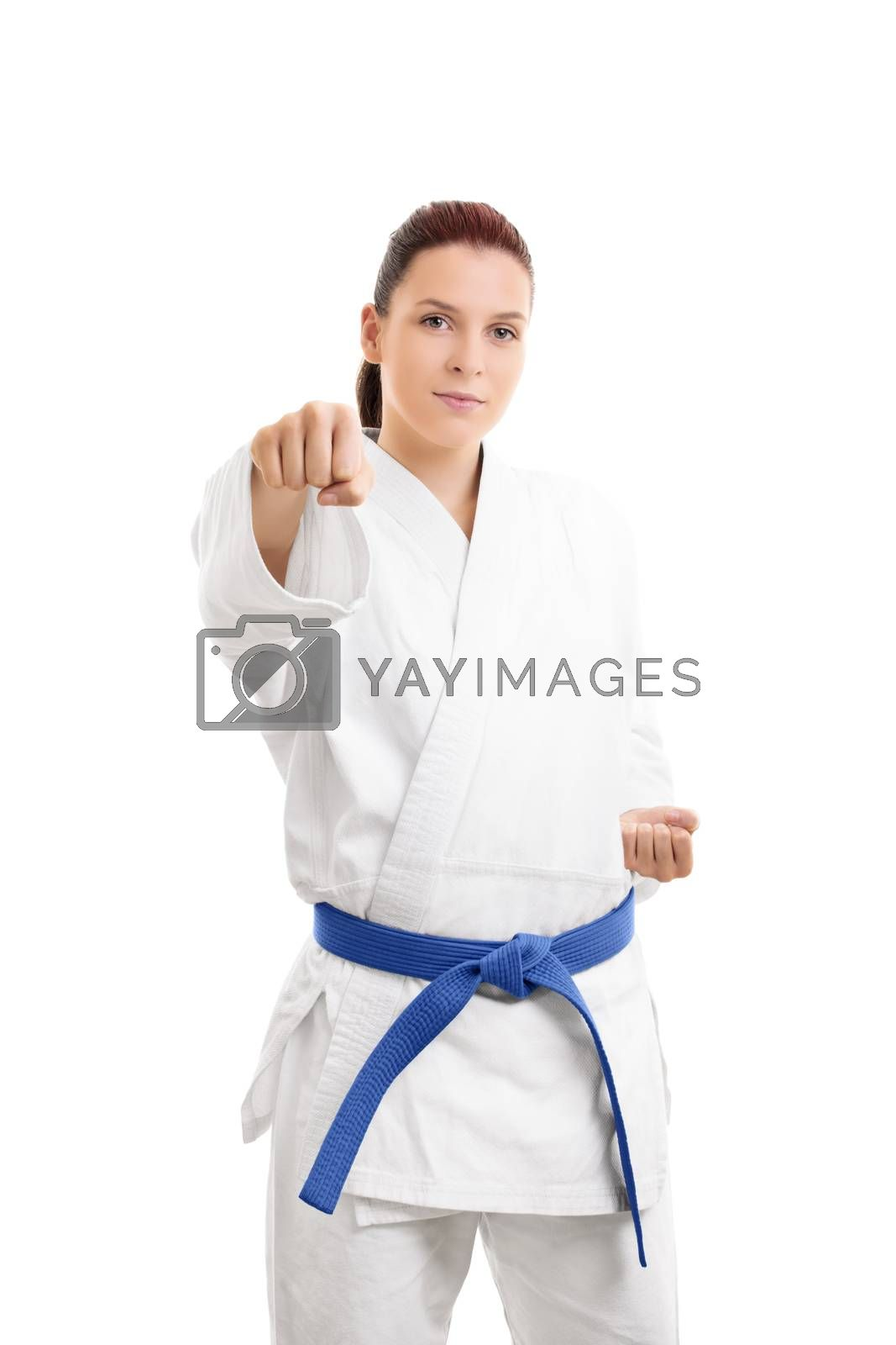 Beautiful young girl in white kimono with blue belt in a stance with the fist up, isolated on white background.