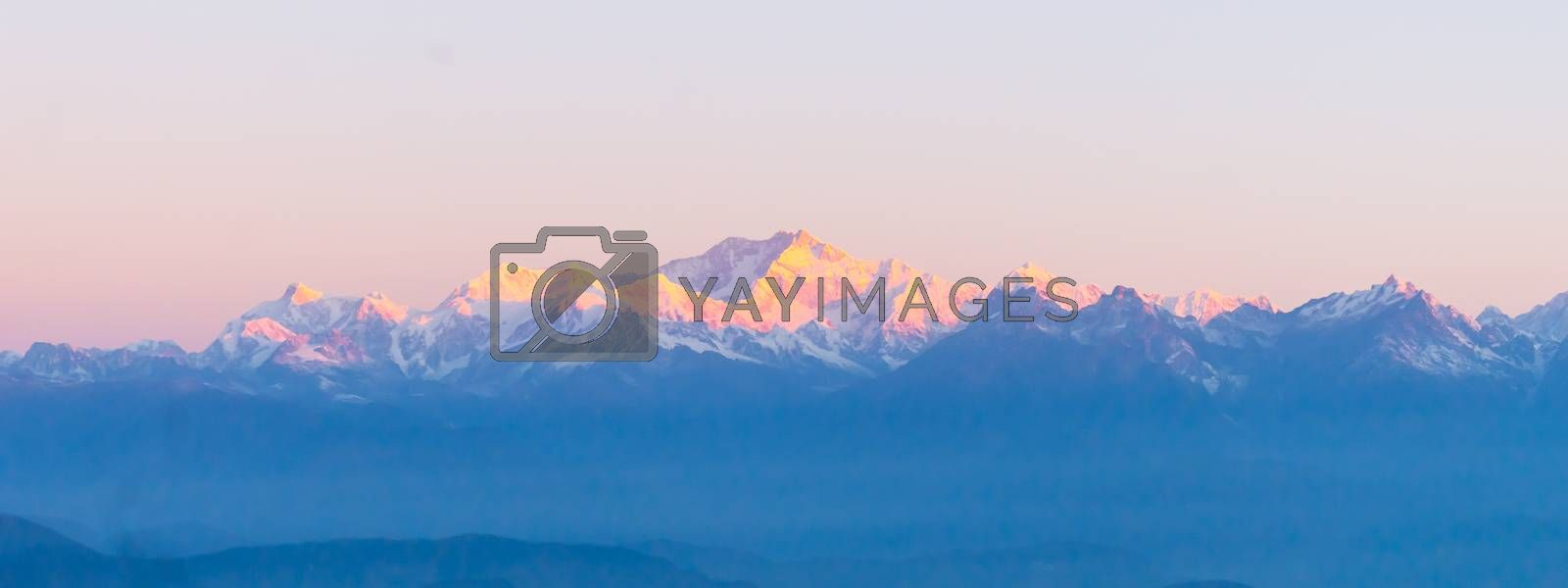 Panorama of majestic Mount Kanchendzonga range of himalayas at first sunrise from Tiger Hill. First ray of sun struck mountain starting beautiful day on entire nature around. Darjeeling, Sikkim, India