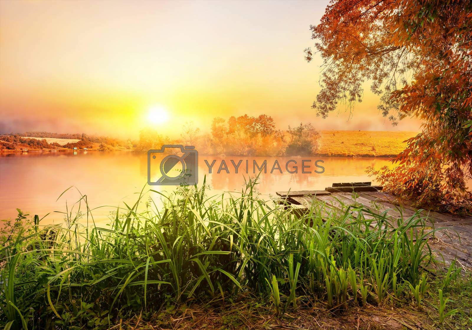 Fishing equipment on wooden pier and calm river in the morning