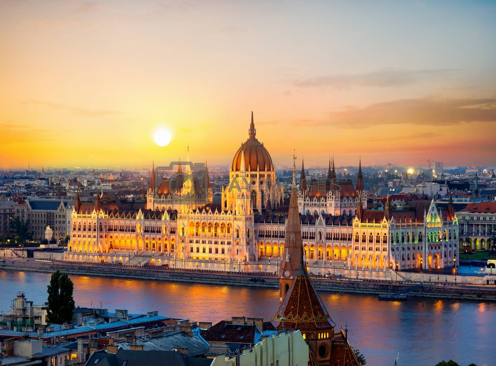 Hungarian parliament on riverbank of Danube illuminated in evening, Budapest