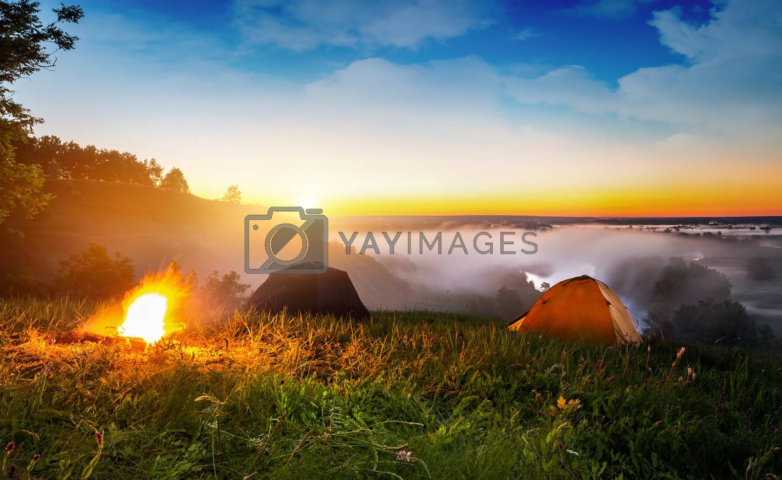 Tents and bonfire in steppe near river at sunrise