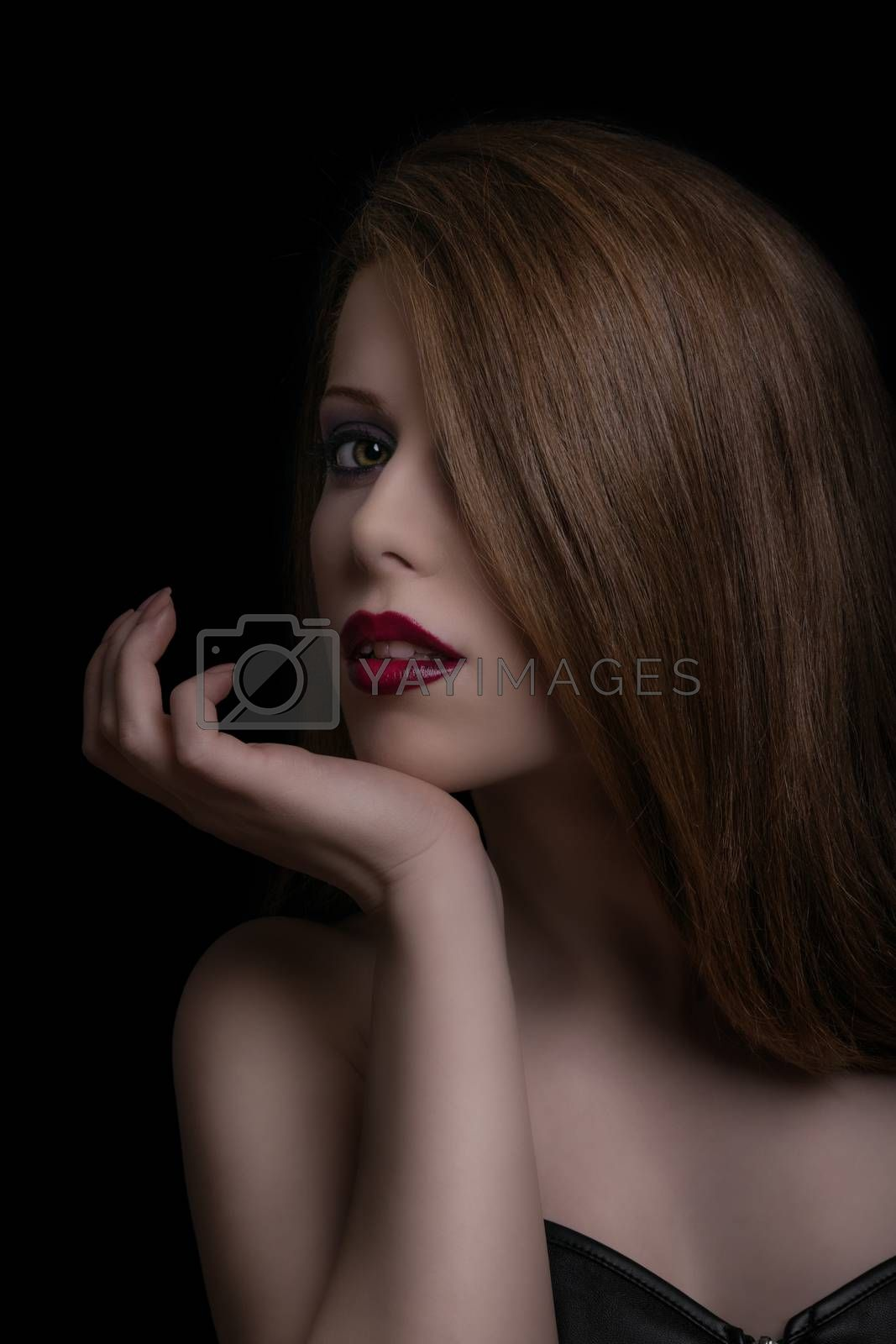 Low key sensual, make up and beauty portrait of a young woman with red lipstick on black background.