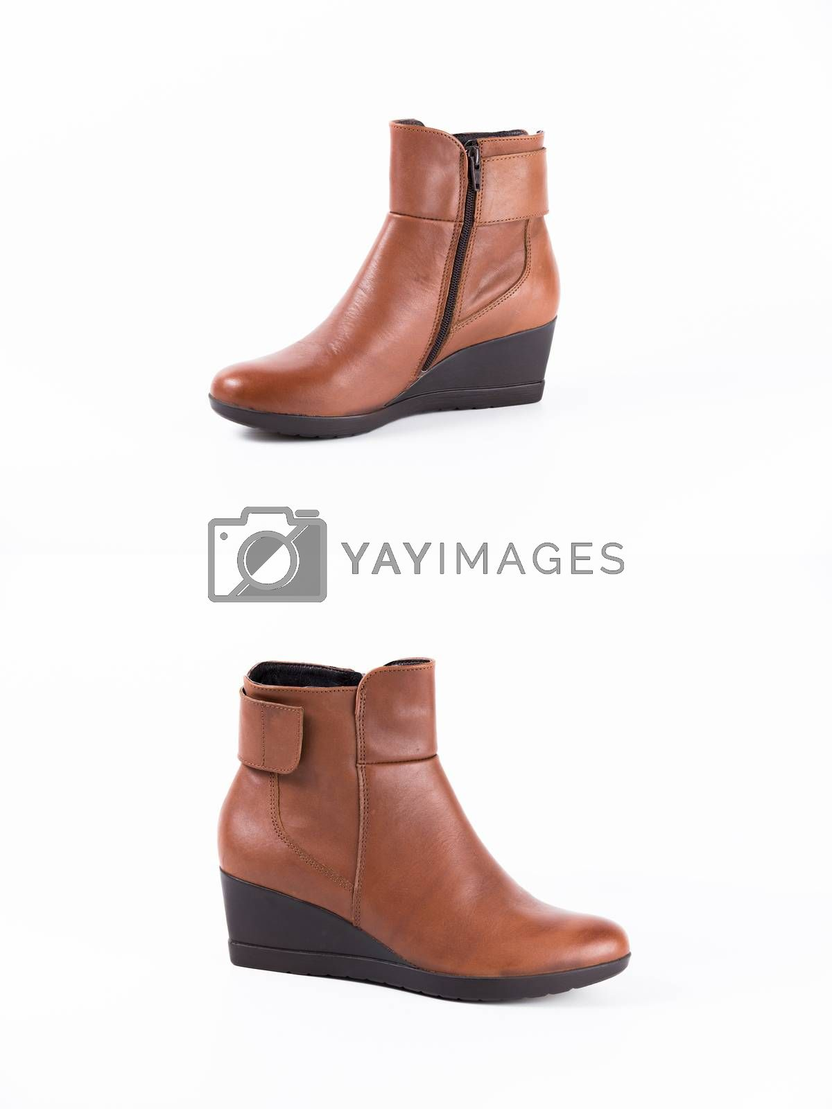 Pair of brown leather boots on white background, isolated product, top view.