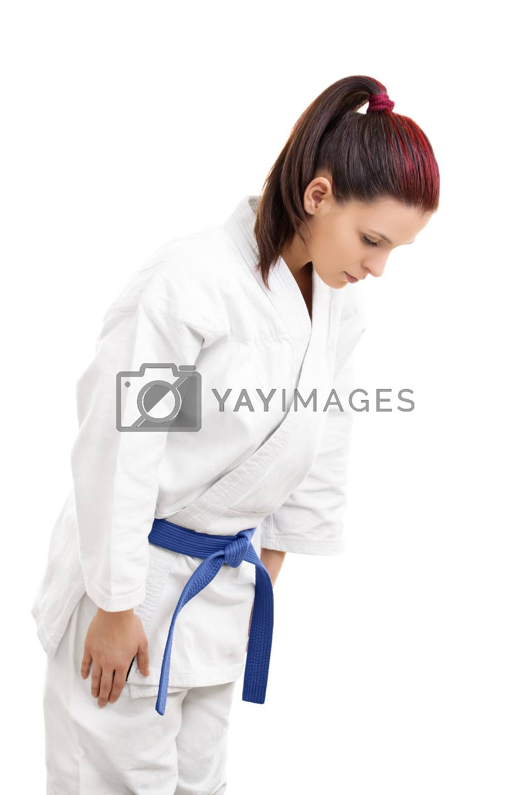 Portrait of a young girl in a white kimono with blue belt bowing, isolated on white background.