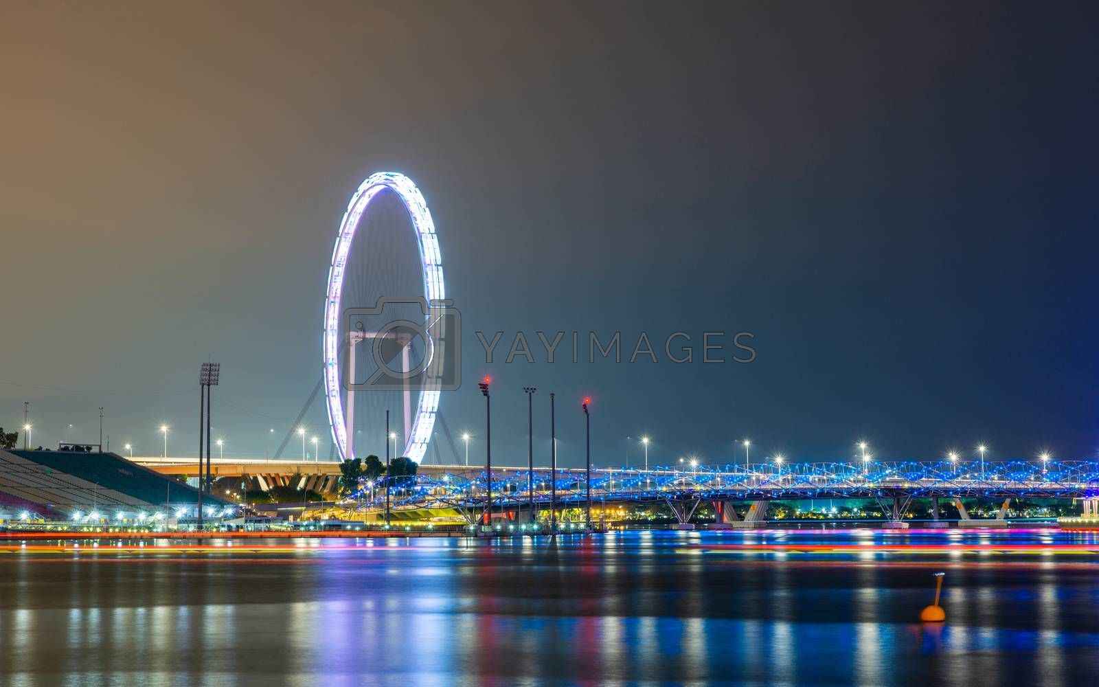 The Singapore Flyer and Helix Bridge at night, colorful lightrails created by boats.