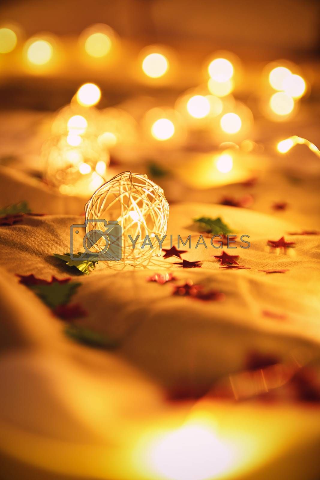 Close up shot of blurred golden Christmas lights with tiny stars and Christmas tree decorations, on rumpled bed sheets, making cozy and festive atmosphere. Festive bukeh background with lights.