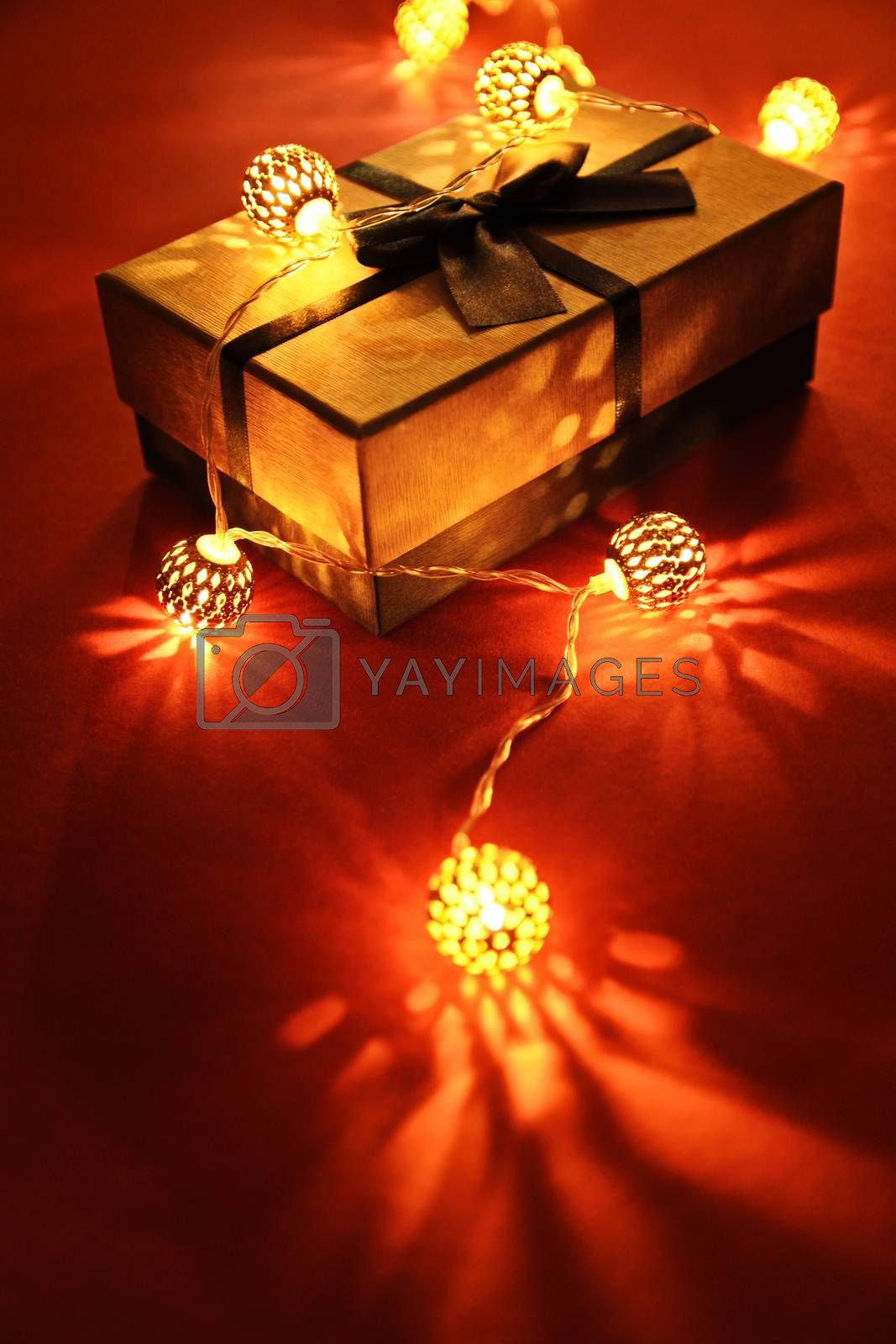 Close up shot of a wrapped gift under glowing Christmas lights on red background, making festive and romantic atmosphere.  Christmas, birthday, anniversary, new year, Valentine's day, date concept.