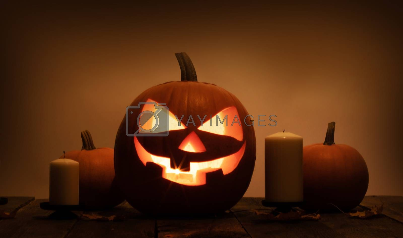 Group of Halloween pumpkin head jack o lantern and candles on dark wooden background