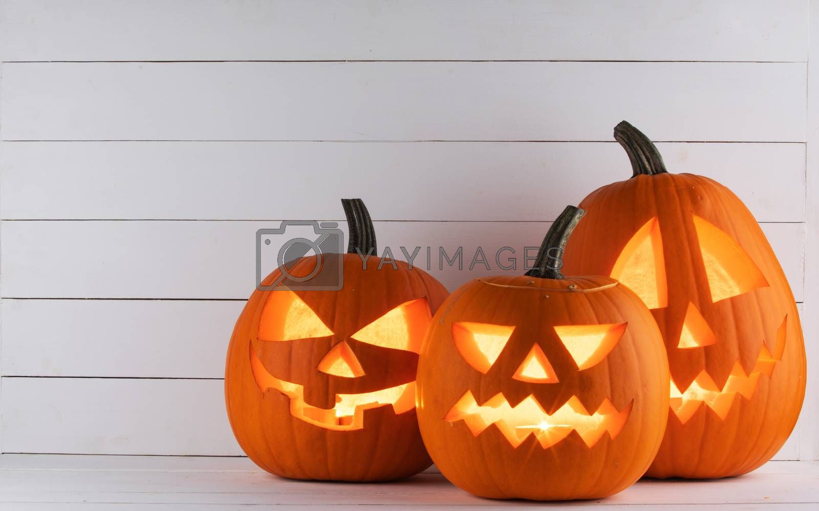 Three Glowing Halloween pumpkins head jack lantern on white wooden background