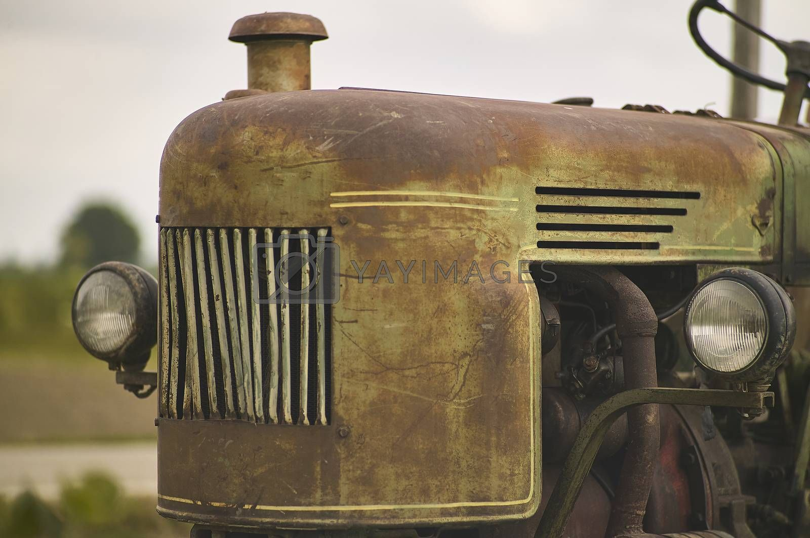 Detail of Old vintage tractor worn and with signs of time in a field ready for another hard day's work
