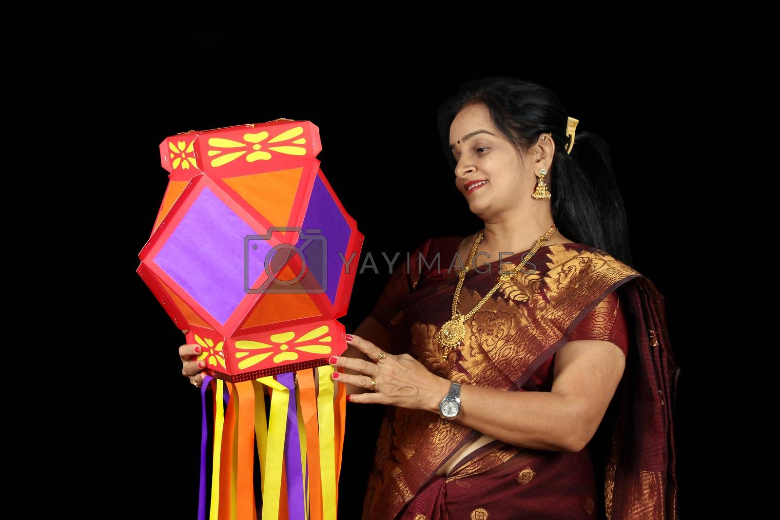 An Indian woman happy with her colorful traditional lantern during Diwali festival in India.