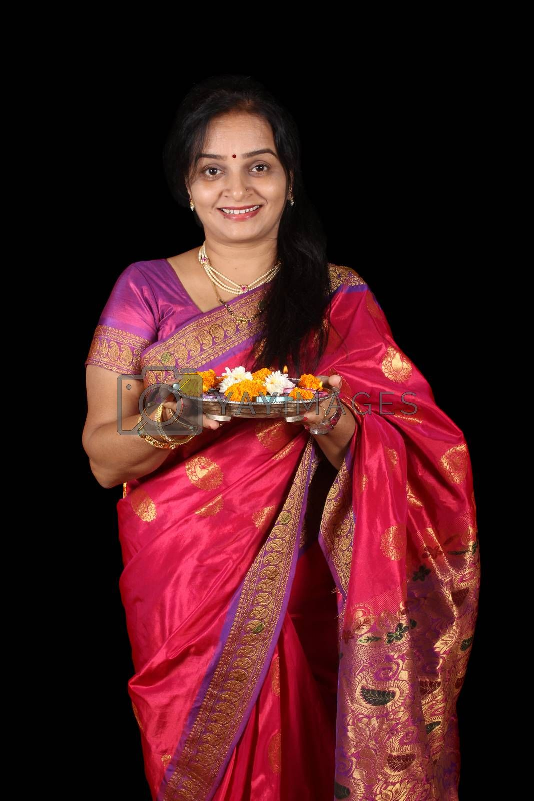 A beautiful middle aged Indian woman smiling happily while holding a traditional plate of Hindu rituals for Diwali festival in India.
