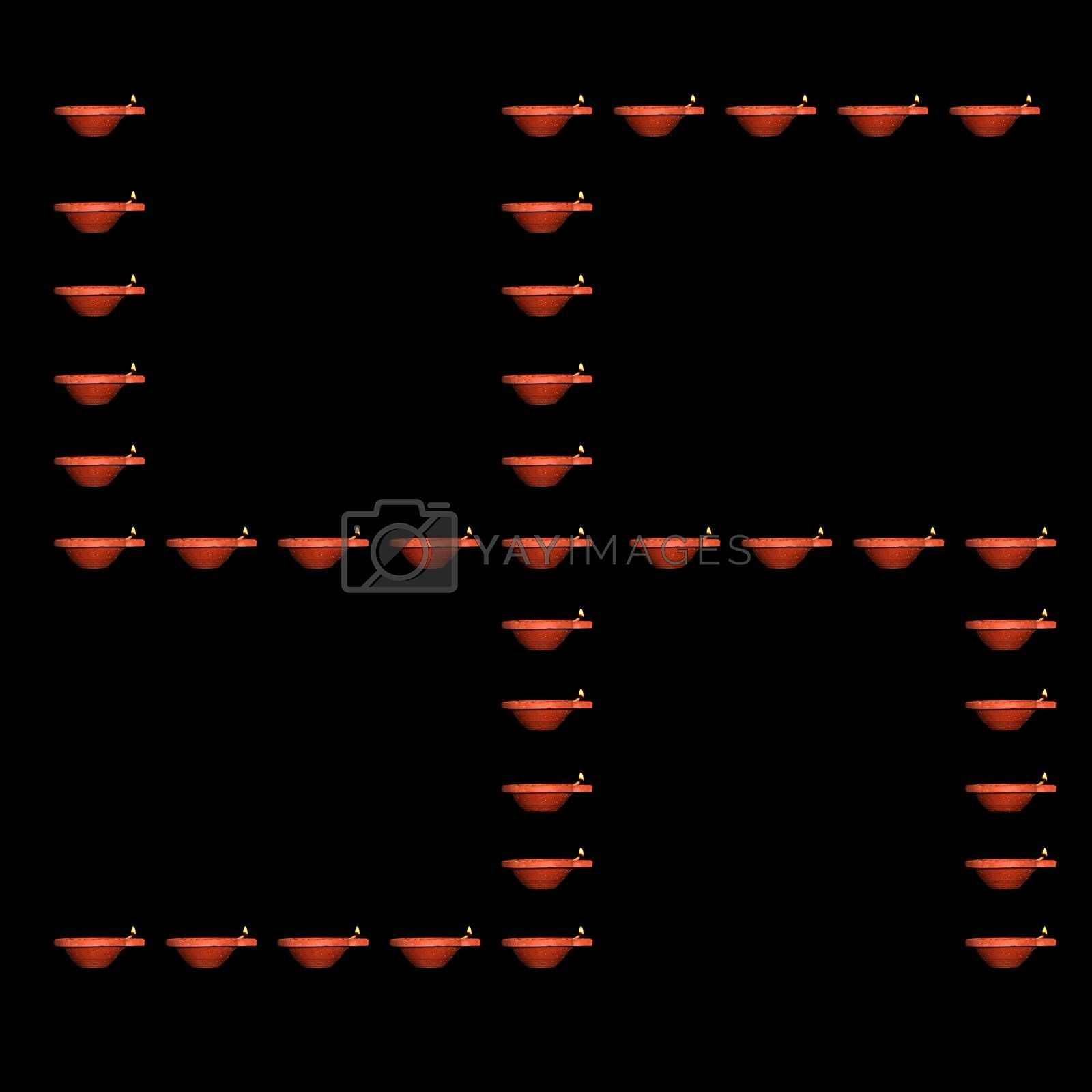The holy Hindu auspicious symbol of Swastika made of traditional earthen Diwali Lamps on black background.