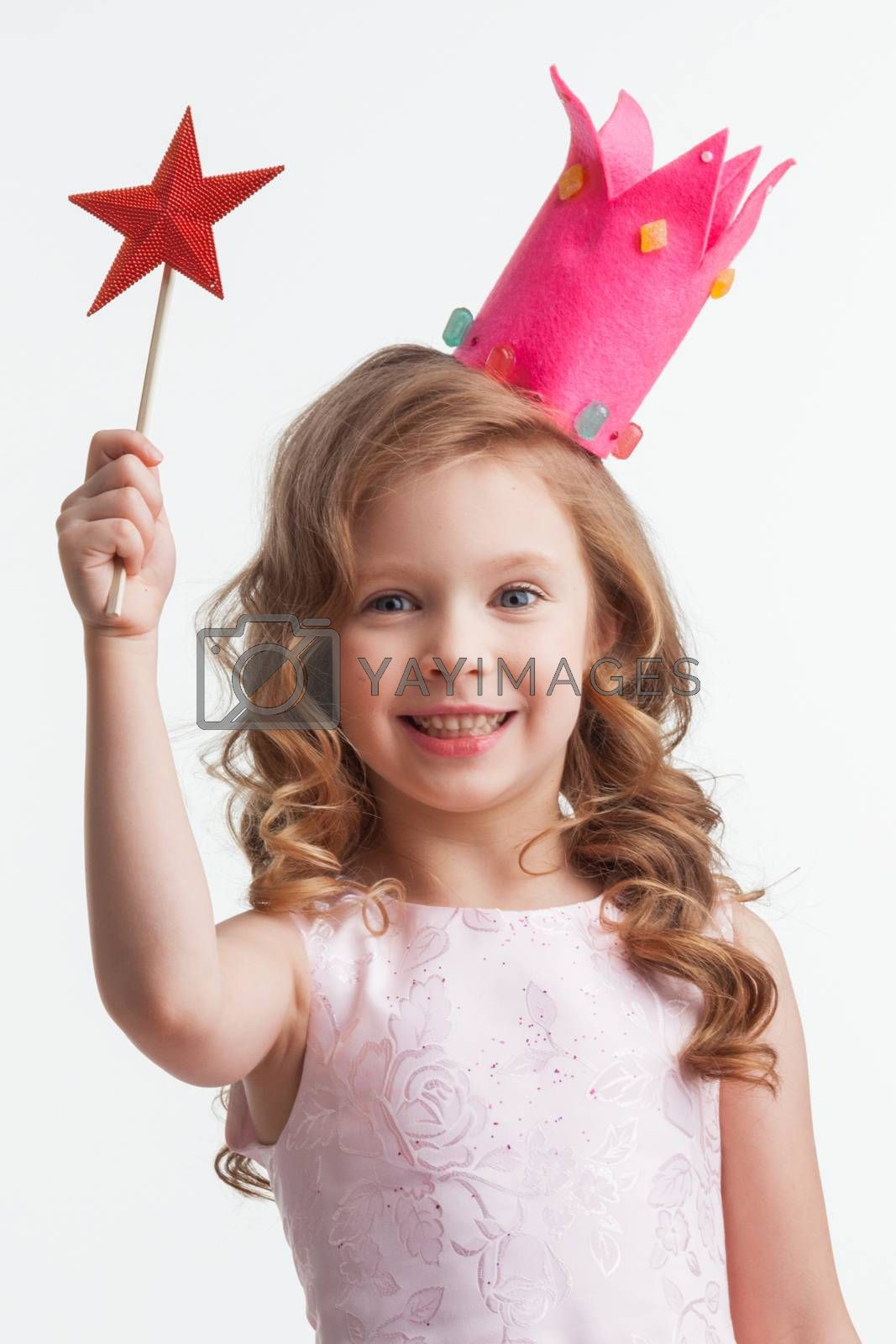 Beautiful little candy princess girl in crown holding star shaped magic wand