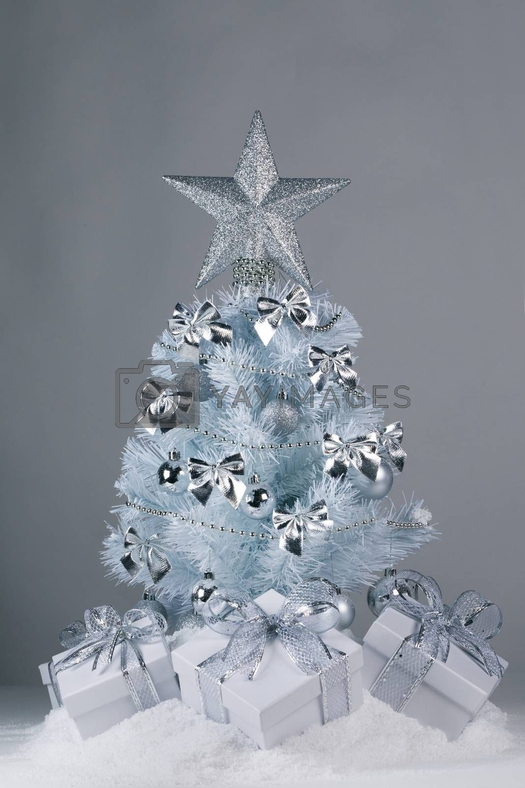 White christmas tree with silver decorations and gifts on snow on gray background