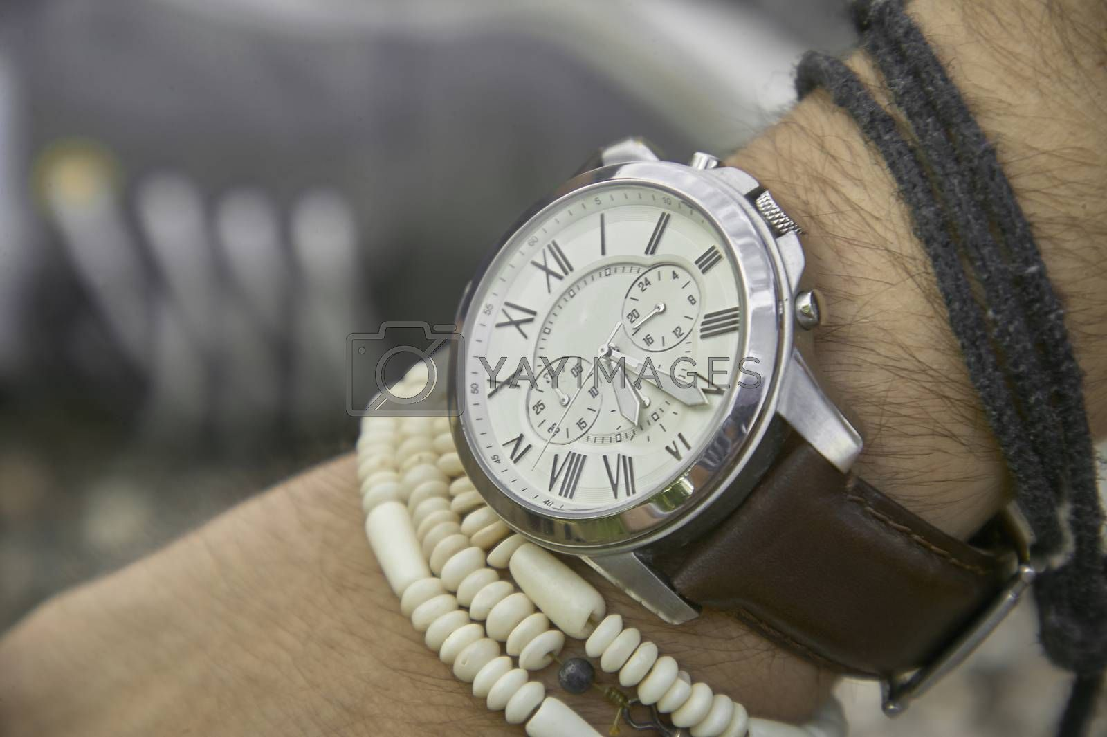 Detail of a vintage wristwatch worn by a boy with other bracelets, symbol of time passing. A great acession for a perfect outfit.