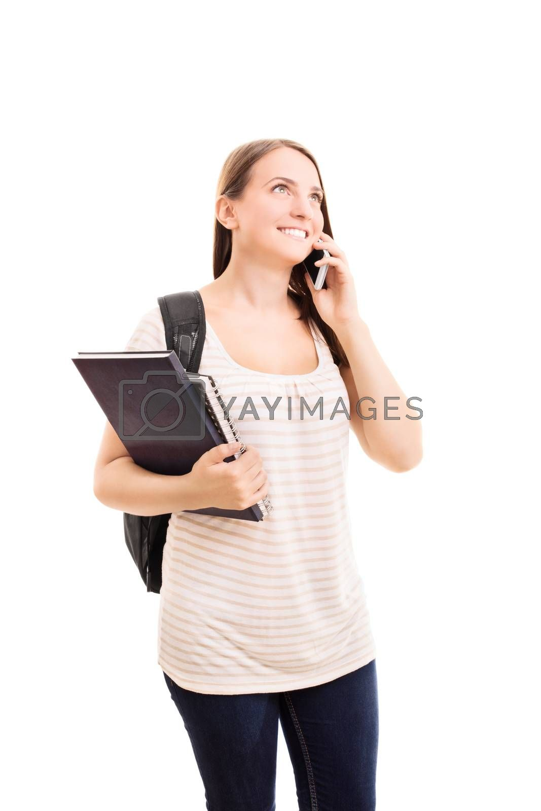 Smiling beautiful young student girl with a backpack, holding books and talking on a phone, isolated on white background.
