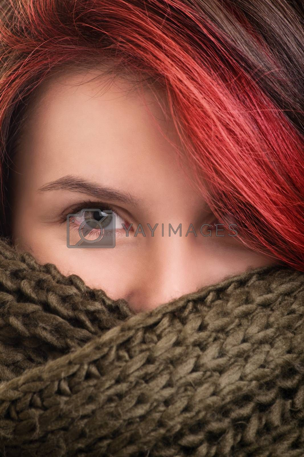 Under the comfort and softness of winter clothes. Close up shot of a beautiful young girl wrapped in a soft and comfy green woolen scarf.