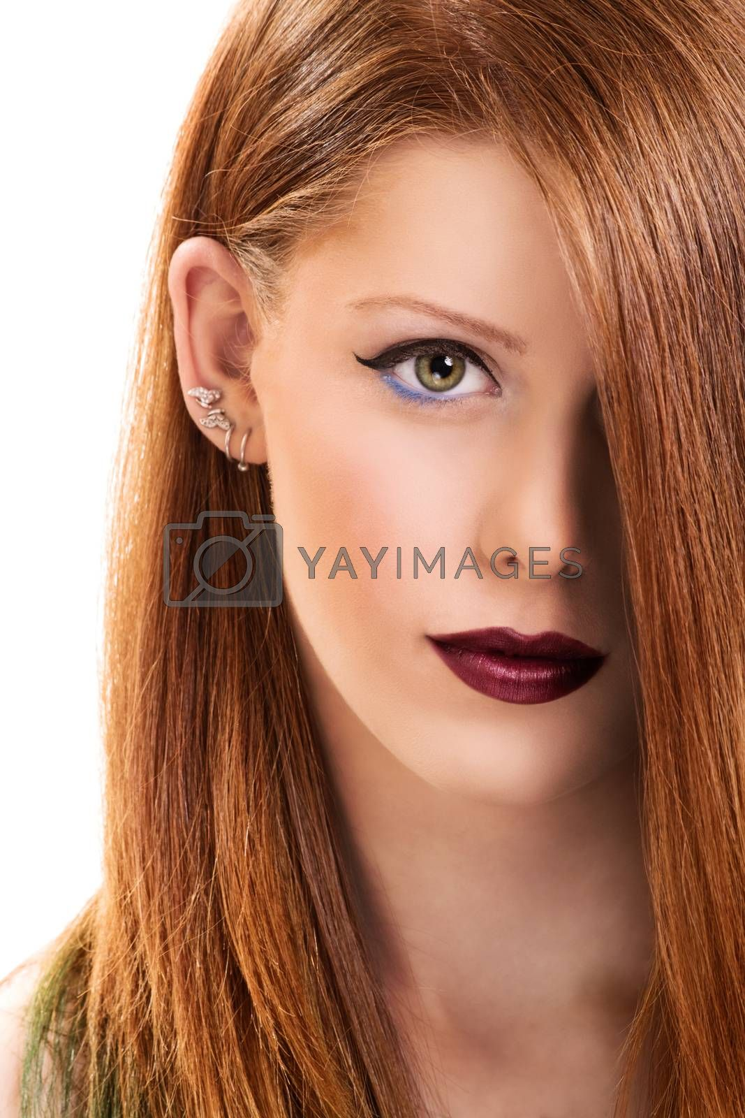 Close up portrait of a beautiful young woman with make up with hair covering her eye, isolated on white background.