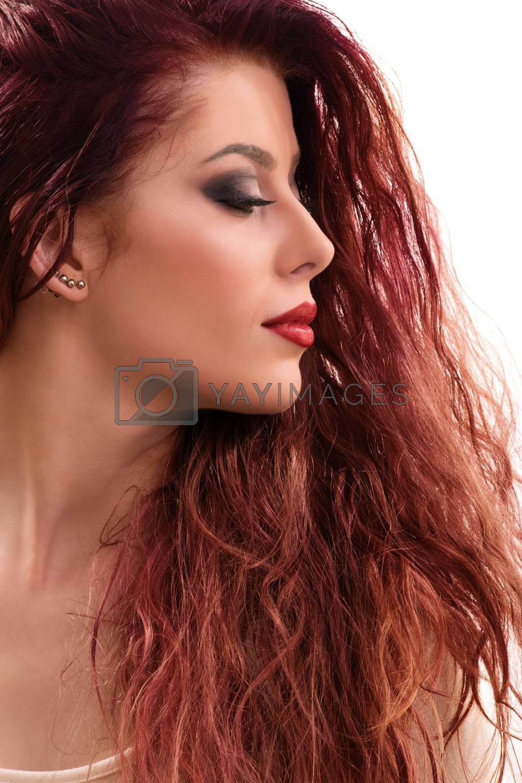 Close up profile shot of a sensual beautiful redhead young woman with smoky make up with closed eyes, isolated on white background.