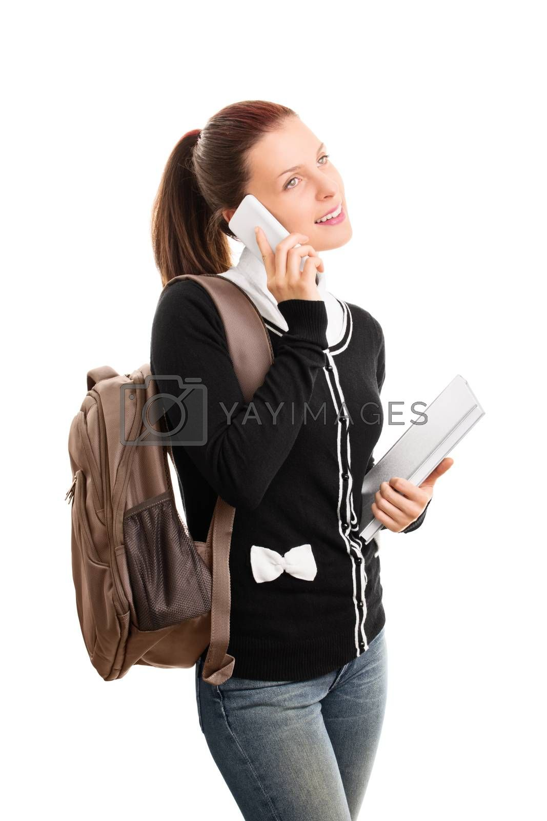 Beautiful smiling young student girl with a backpack, holding books and talking on a phone, isolated on white background.
