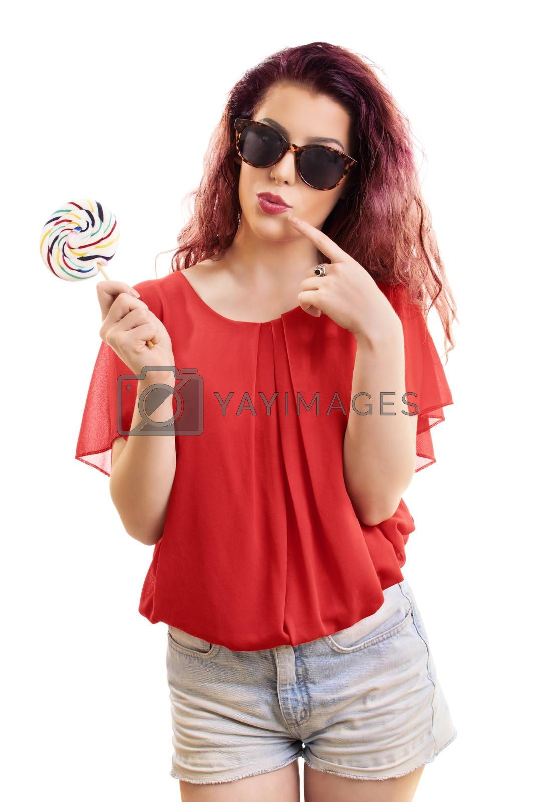 Beautiful young redhead girl with sunglasses holding a colorful lollipop, isolated on white background.