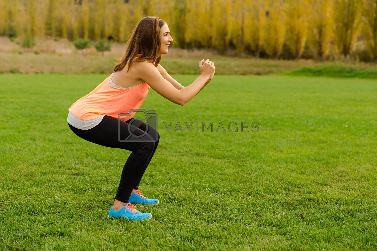 An attractive woman exercising outdoor on a soccer field