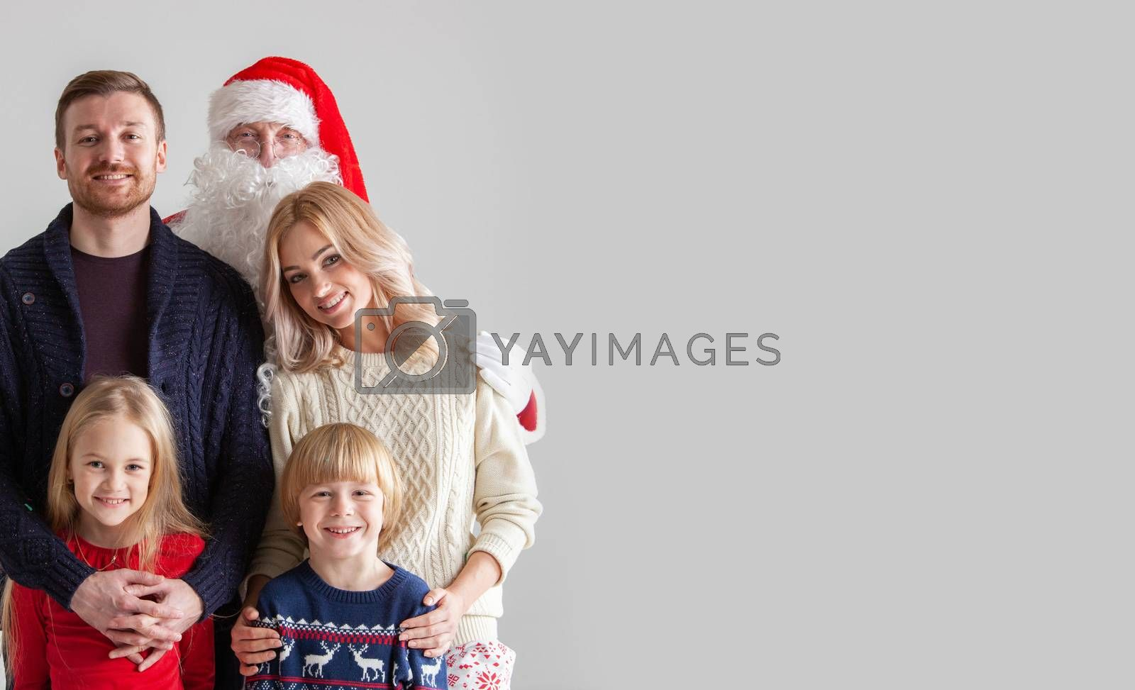Portrait of young family with two children with Santa Claus, gray background with copy space for text