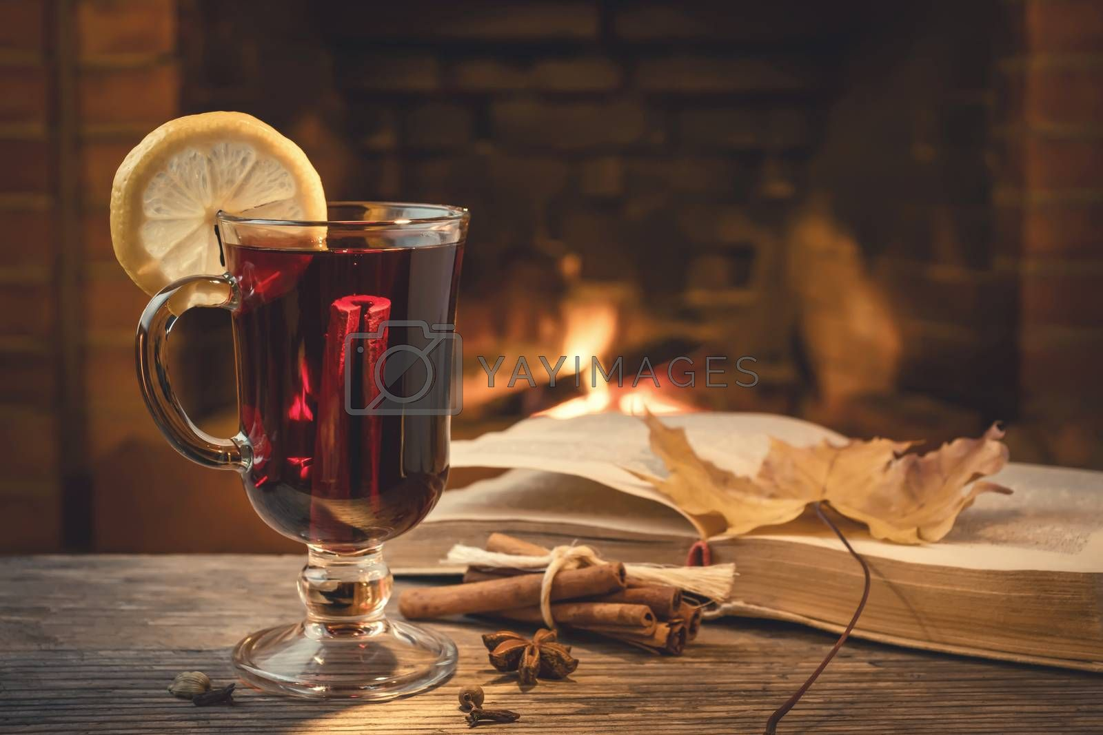 Glass of mulled wine, spices, a book on a table in a cozy room with a burning fireplace.