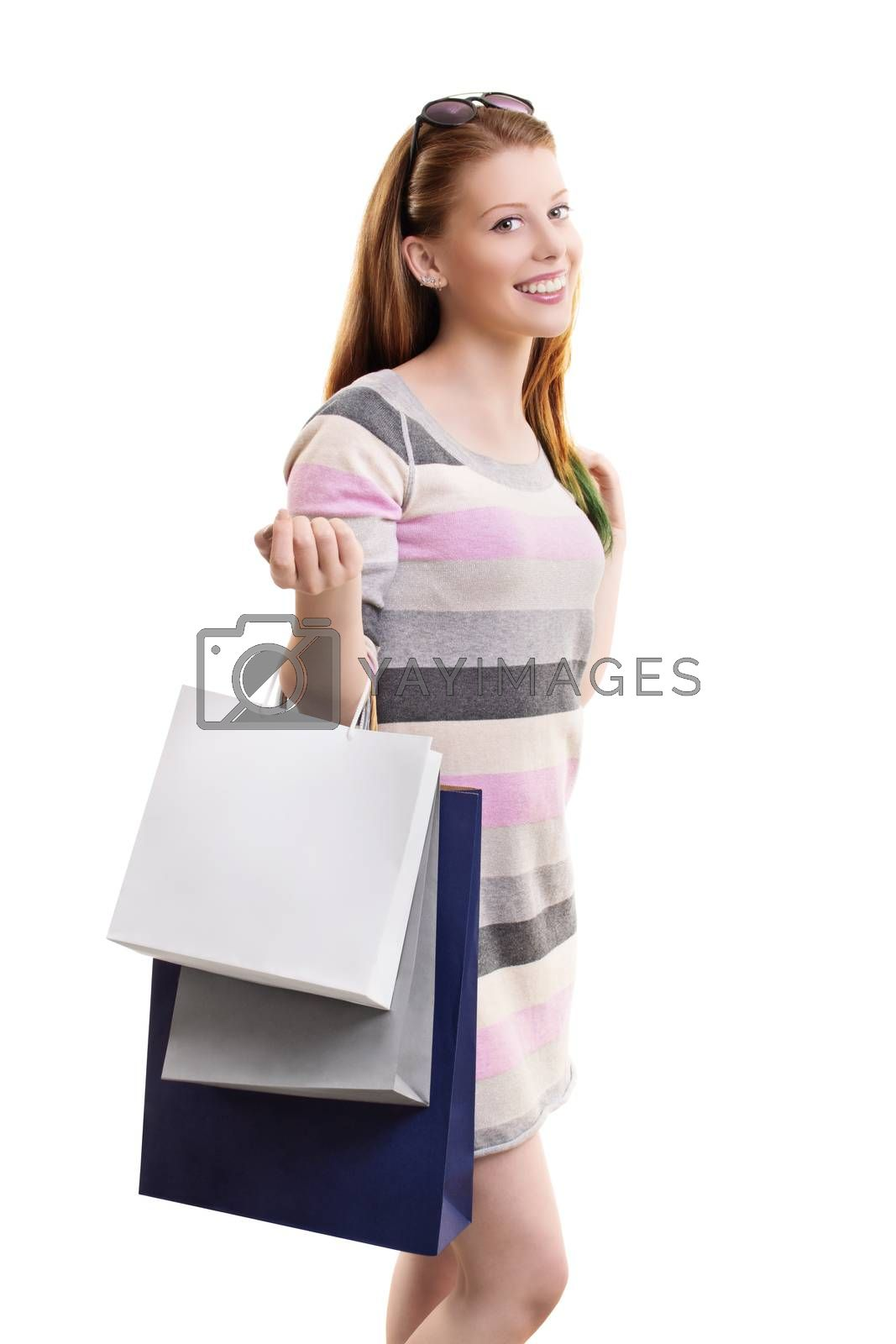 Shopping concept. Portrait of a beautiful smiling young girl in a dress, holding a lot of shopping bags, isolated on white background.