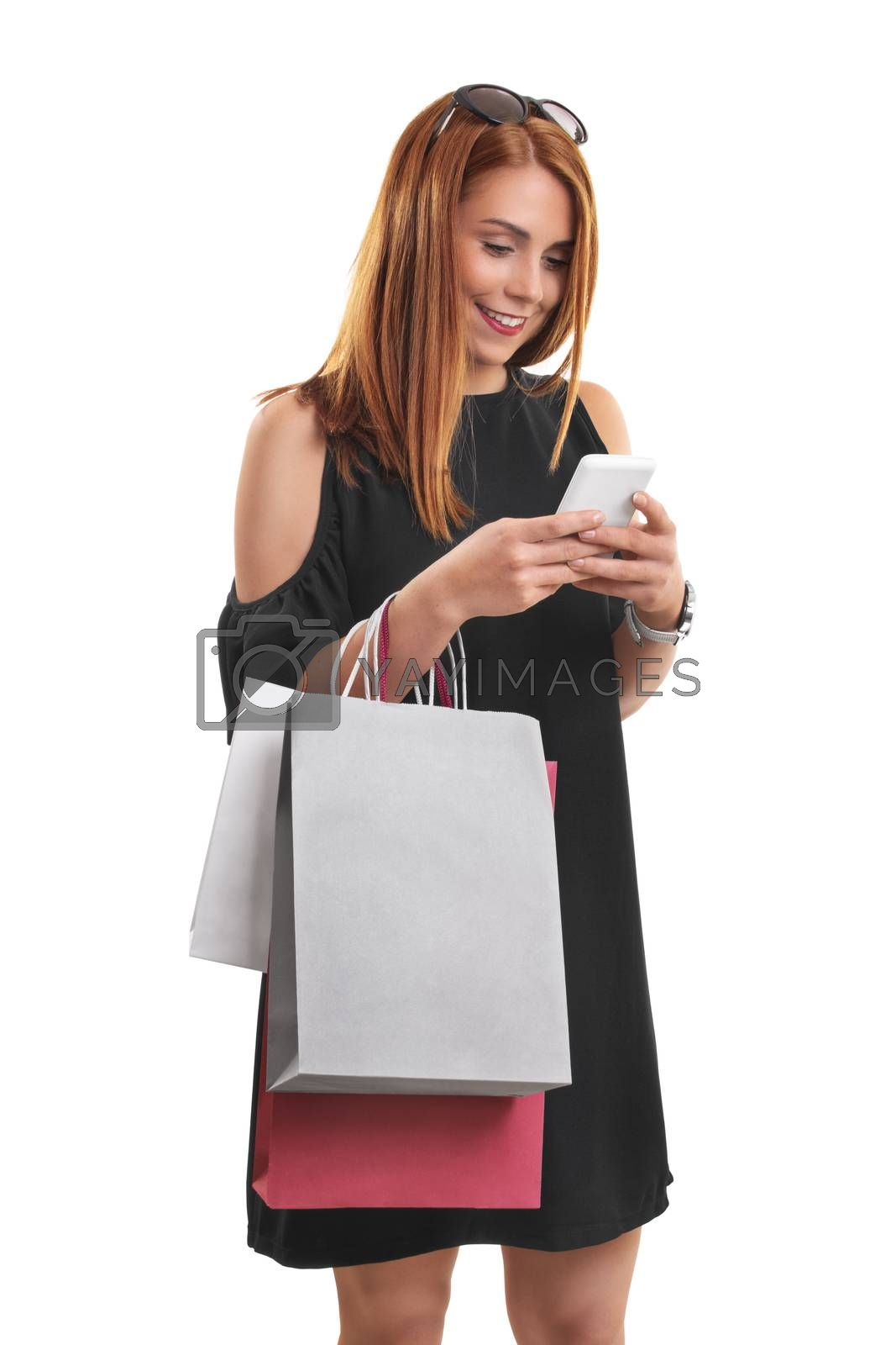 Portrait of a beautiful young girl in a stylish dress looking and typing at her phone, holing shopping bags, isolated on white background.