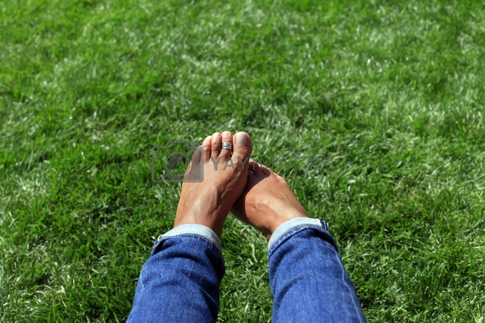 Bare feet in green grass, woman relaxing in nature