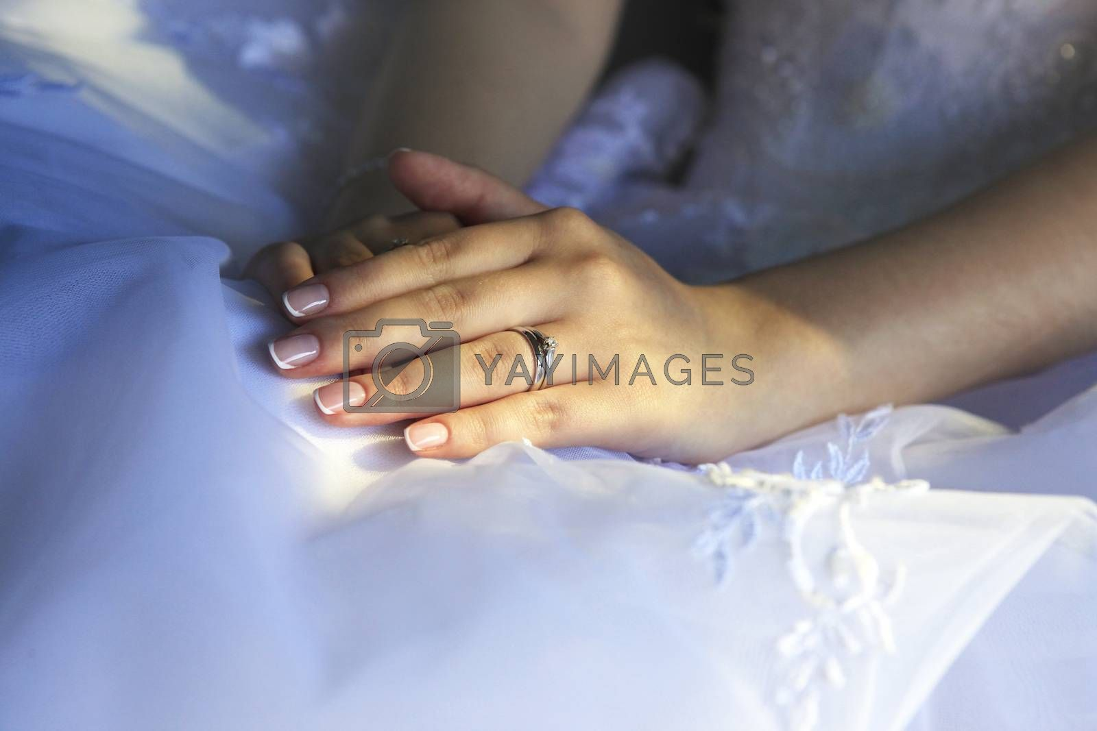 Hands of the bride on a background of a wedding dress