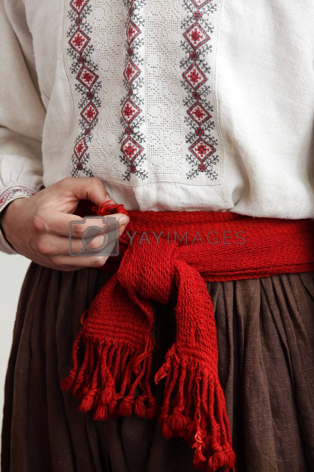 Folk costume. Cossack in an embroidered shirt with a red belt