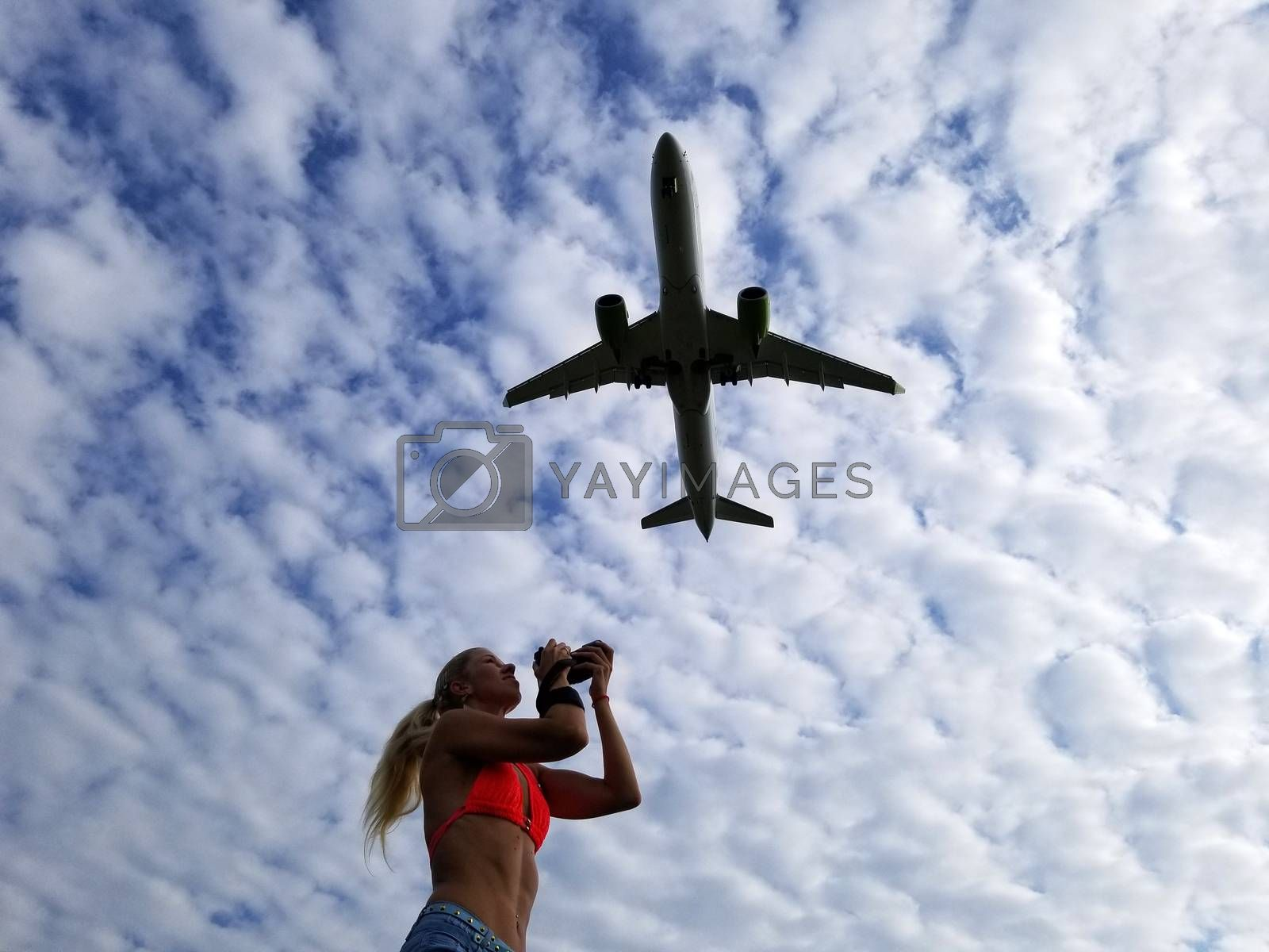 Blonde girl with long hair takes pictures of a plane flying over her on a cloudy sky background.
