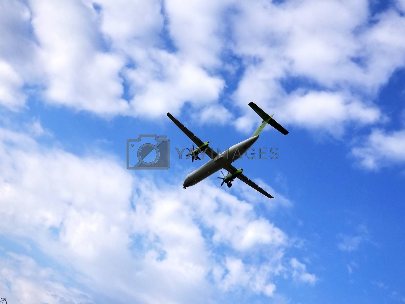 View from above on airplane in flight. Aircraft is flying in blue cloudy sky. Silhuette airplane on the cloudy sky.